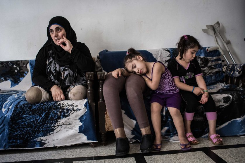 "Hasna and her nieces at home in Tripoli, Lebanon, on June 11, 2014. A bomb in Syria killed her husband and kids in 2012; she received two prosthetics legs. ""It was hard and difficult but now I always try to focus on the positive things."""