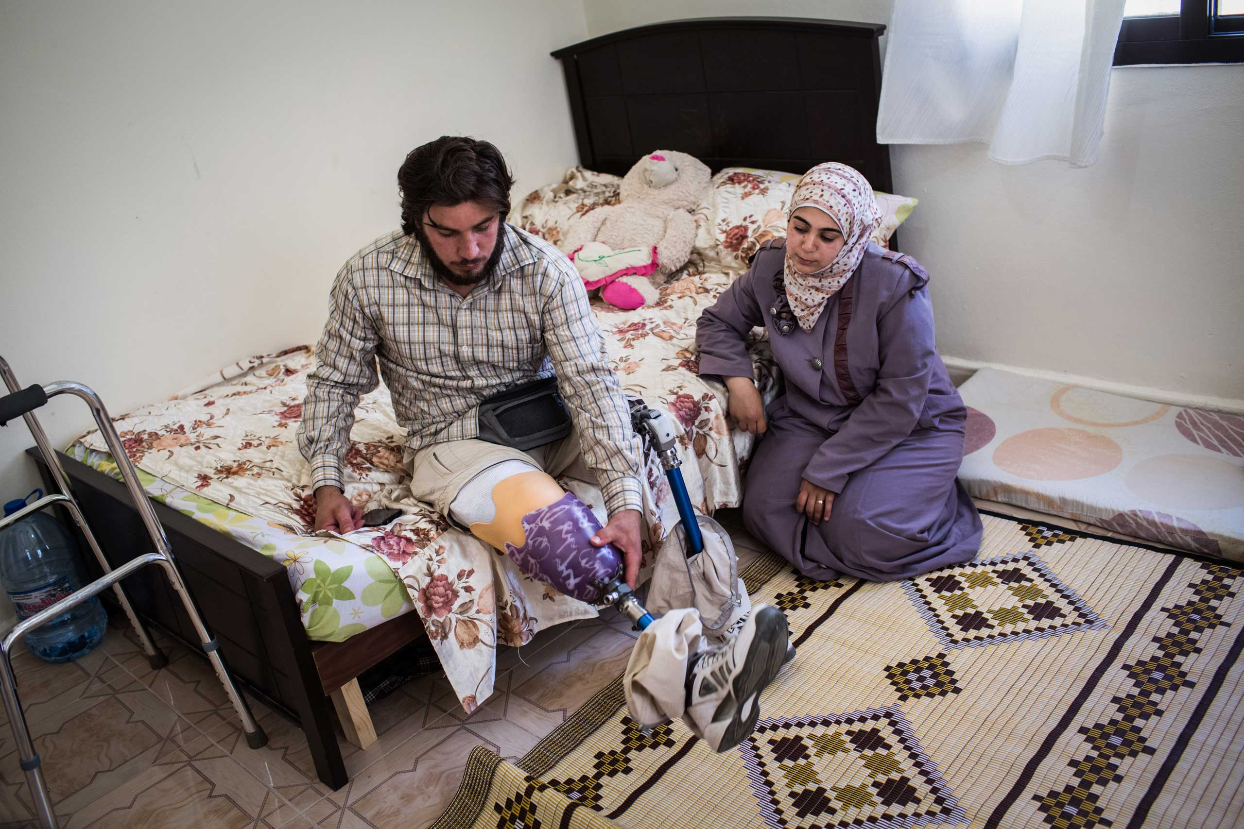 Ahmad, 29, fits his prosthetic with the help of his wife, Lazmiah, at their home in Tripoli, Lebanon, June 17, 2014. Ahmad lost both legs after a mortar attack near his home in Zabadane, Syria. He and his wife volunteer in the area.