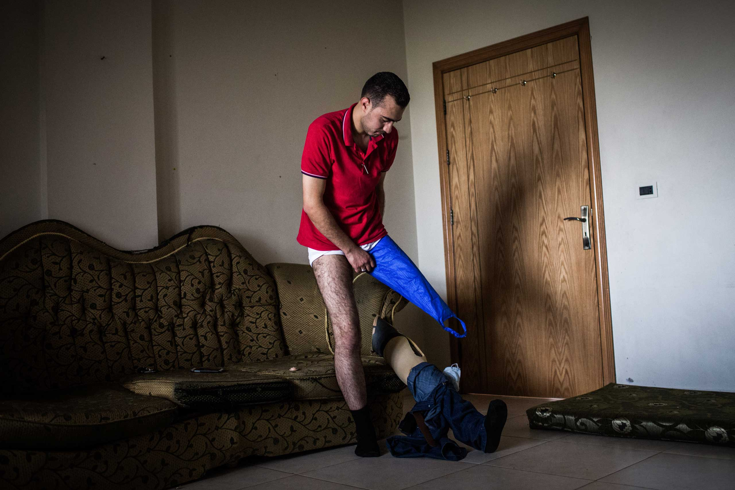 Ihsan fits his prosthetic at home in Qab Elias, Lebanon, June 19, 2014. The dental student, 22, was injured in December 2012 when a bomb fell nearby, leading to two surgeries and the loss of a leg. He continued to volunteer.