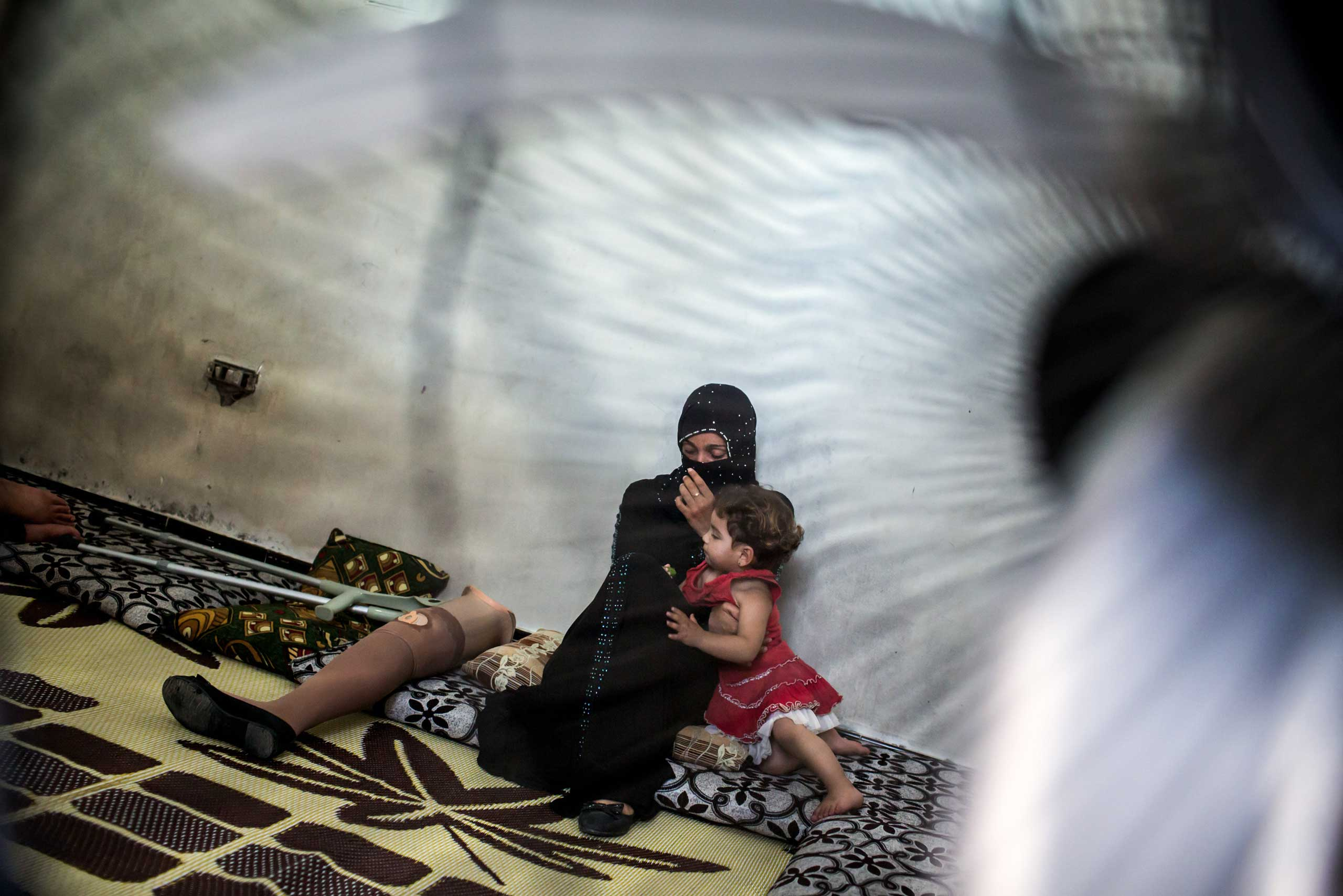 "Awatef, 25, with her daughter, Sabah, 2, at home in Tripoli, Lebanon, June 24, 2014. She lost her leg in shelling near her home in Homs earlier this year. She walked for the first time in six months: ""I keep practicing so it is getting easier."""