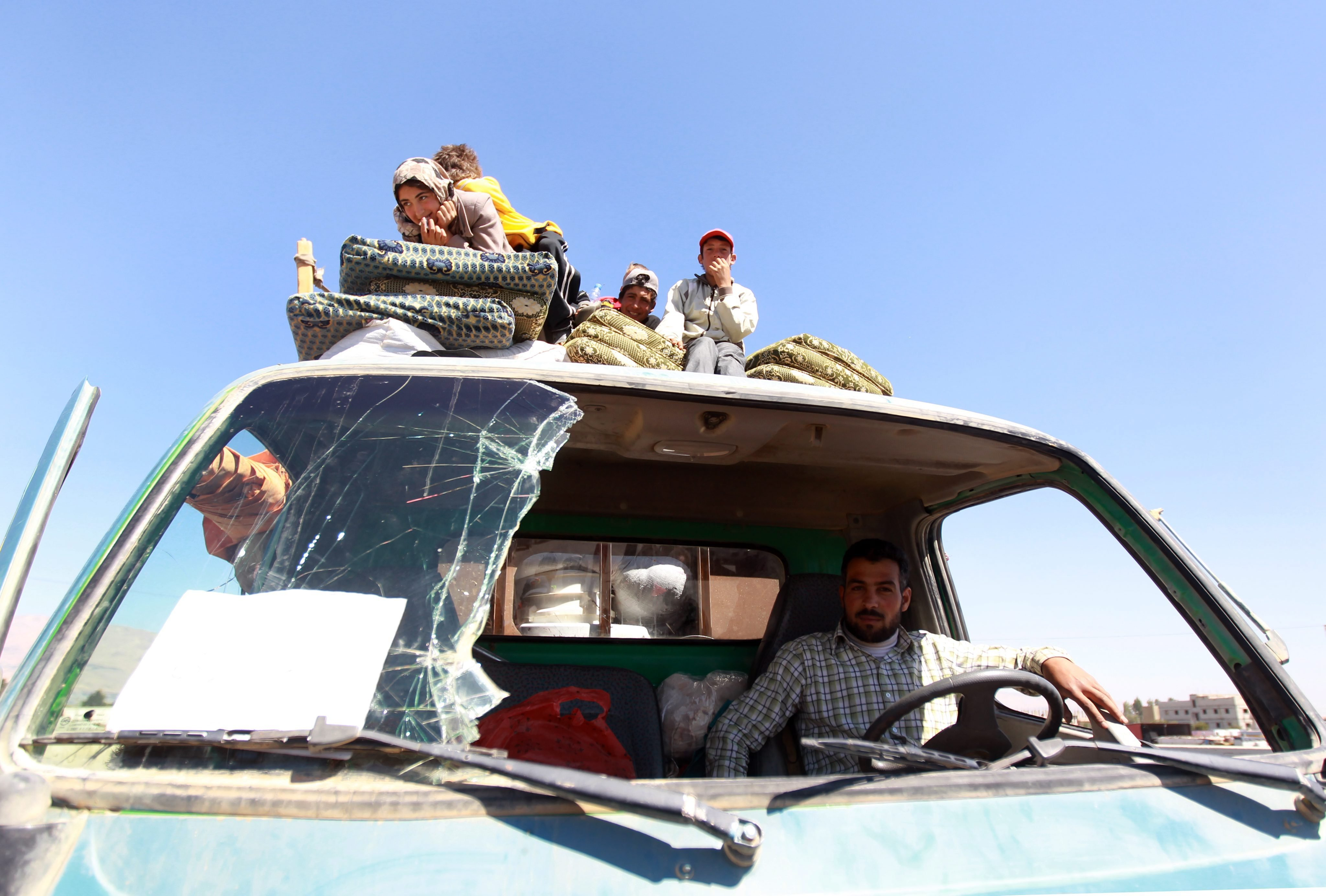 Syrian refugees, who had been based in Arsal but fled after recent fighting, sit on the back of a pick-up truck with their belongings at the Lebanese border crossing point of Masnaa, at Bekaa Valley, Lebanon, Aug. 8, 2014.