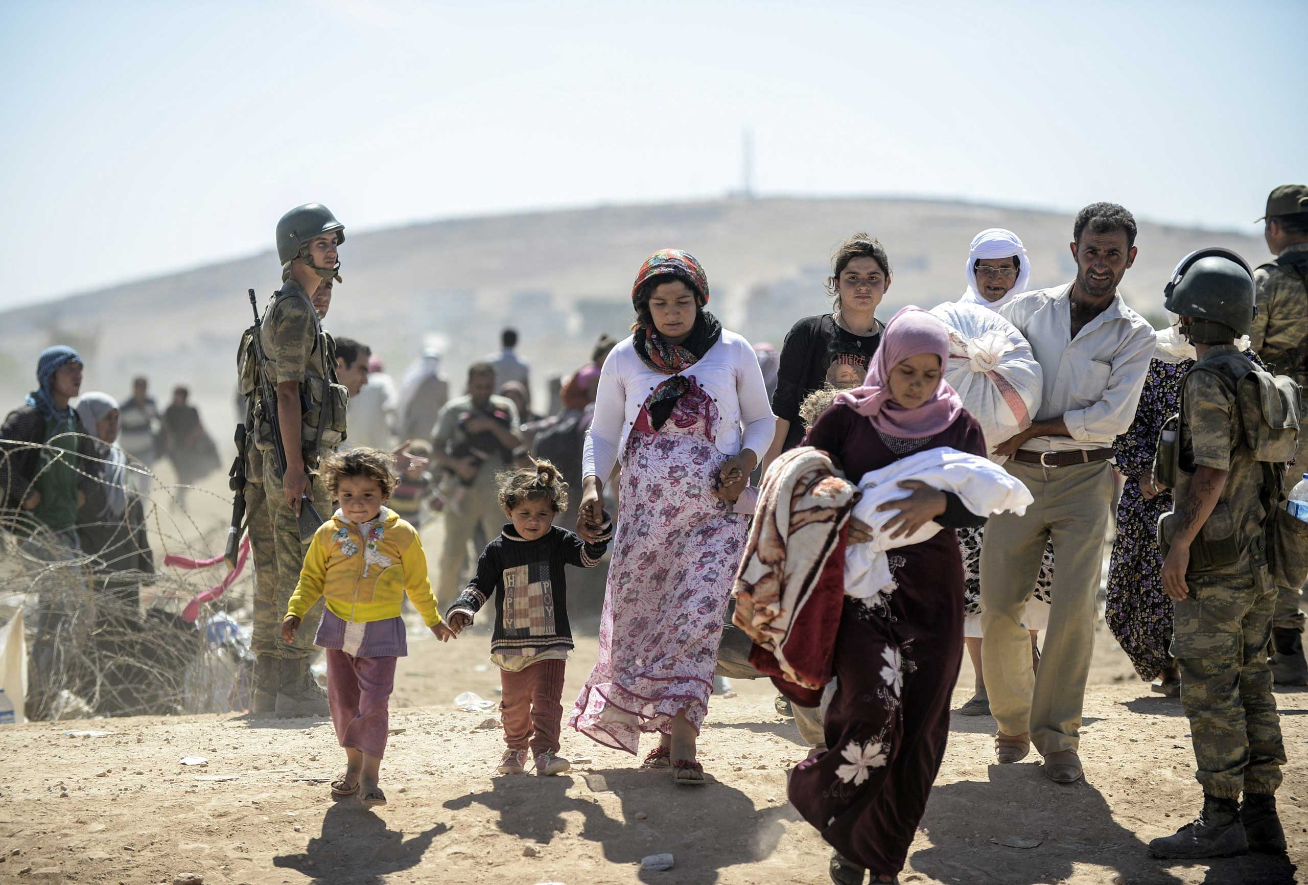 Syrian Kurds cross the border from Syria into Turkey near the southeastern town of Suruc in Sanliurfa province, on Sept. 20, 2014.