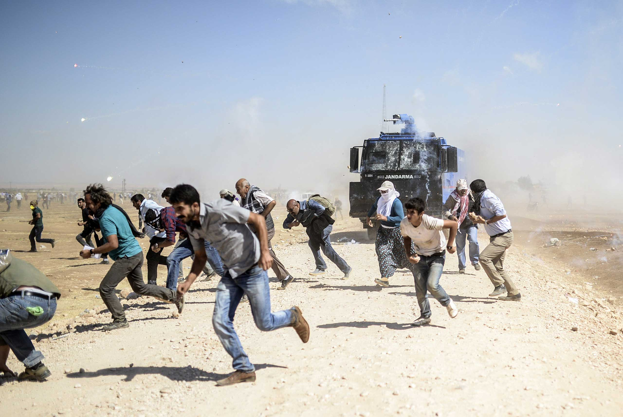 Kurdish protestors clash with Turkish soldiers near the Syrian border after Turkish authorities temporarily closed the border at the southeastern town of Suruc in Sanliurfa province, on Sept. 22, 2014.