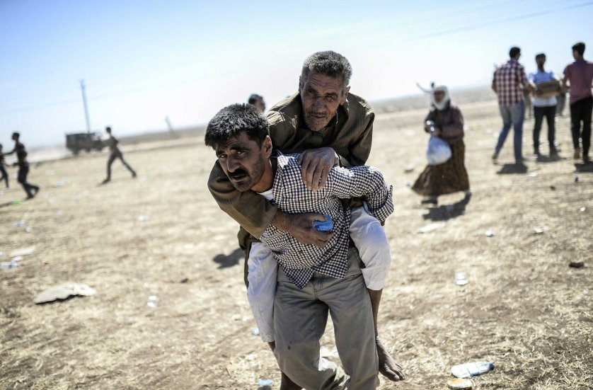 A man carries an elderly Syrian Kurd after they crossed the border between Syria and Turkey near the southeastern town of Suruc in Sanliurfa province, on Sept. 20, 2014.