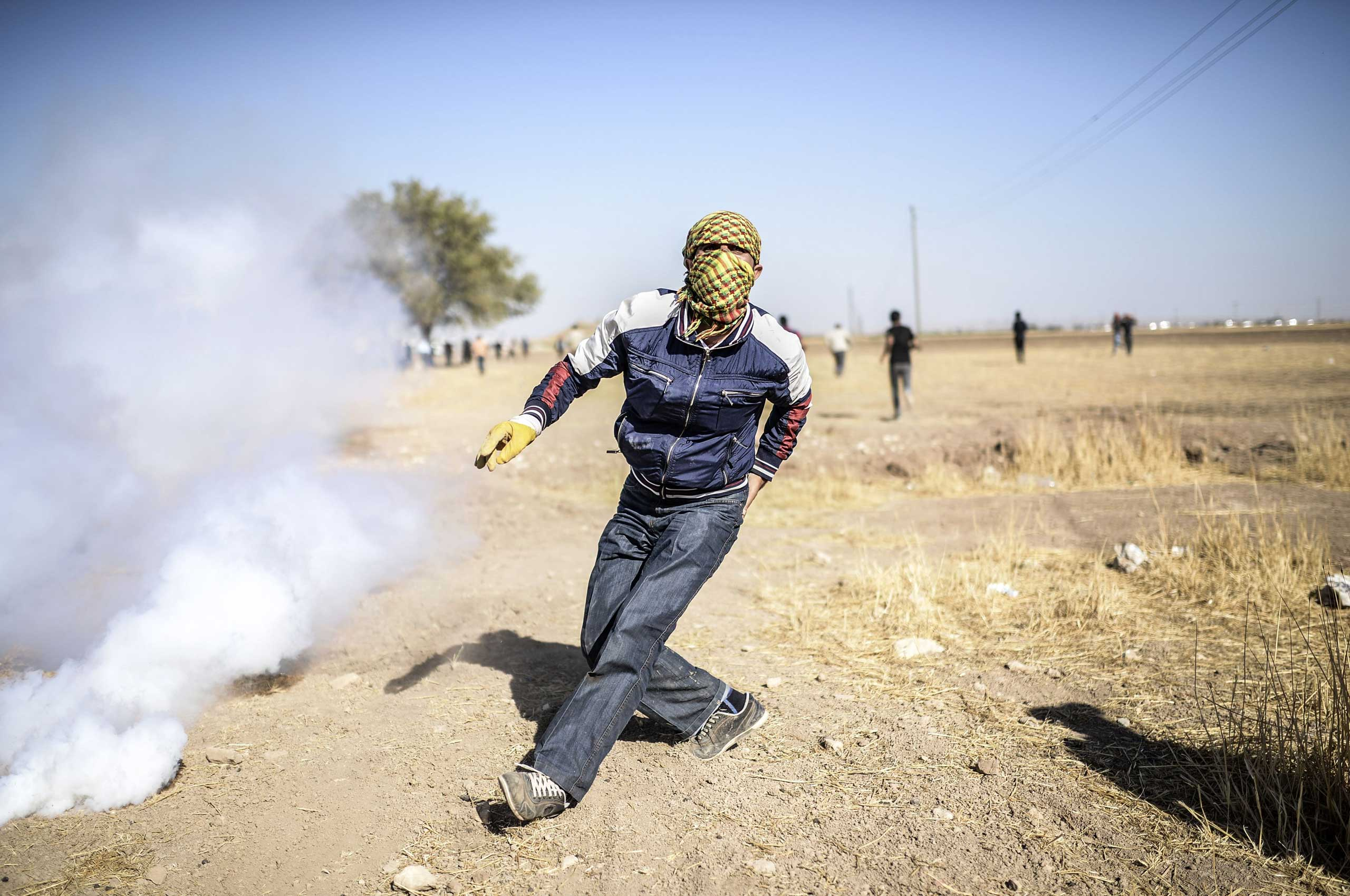 A Kurdish protestor clashes with Turkish soldiers (unseen) near the Syrian border after Turkish authorities temporarily closed the border near the southeastern town of Suruc in Sanliurfa province, on Sept. 22, 2014.