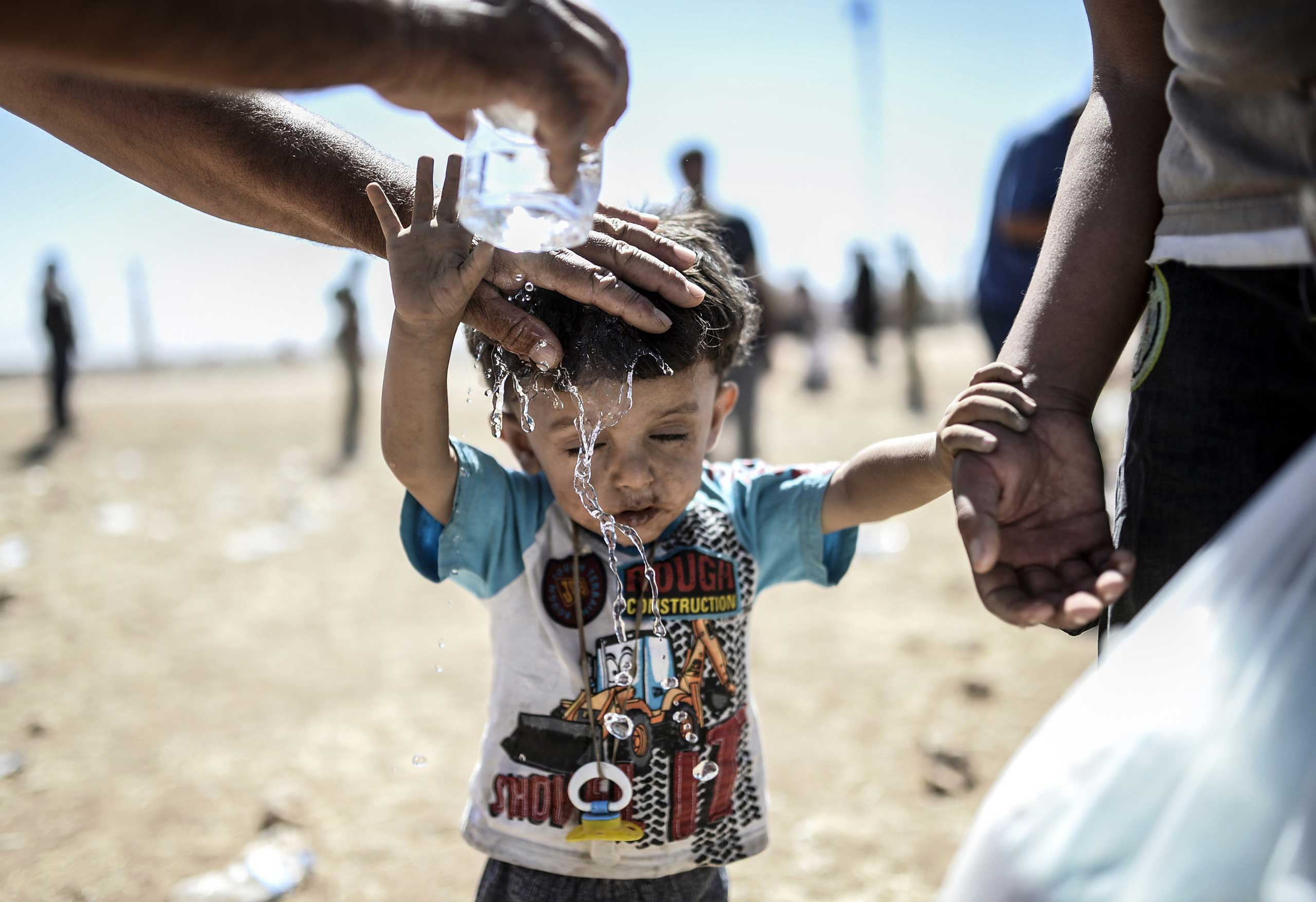 A Syrian Kurd pours water on a child after they crossed the border between Syria and Turkey near the southeastern town of Suruc in Sanliurfa province, on Sept. 20, 2014.
