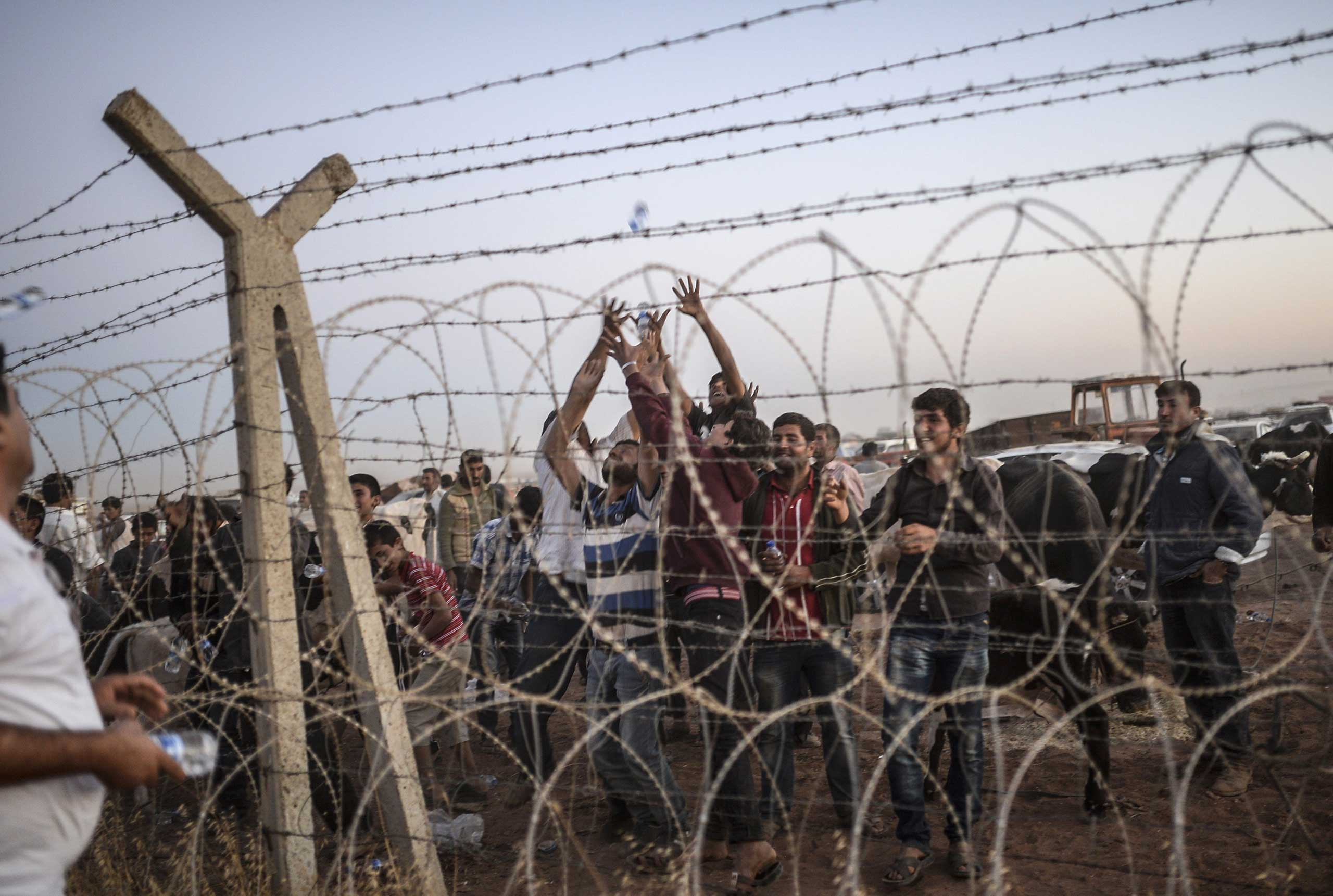 Syrian Kurds try to grab water thrown from Turkey near the border with Syria as they wait to take care of their animals at the southeastern town of Suruc in Sanliurfa province, on Sept. 21, 2014.