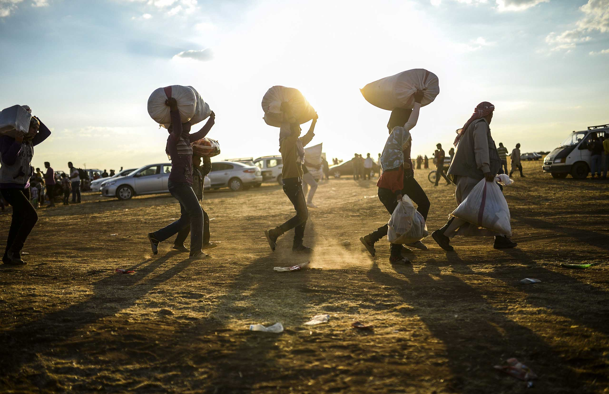 Syrian Kurds carry belongings as they cross the border between Syria and Turkey near the southeastern town of Suruc in Sanliurfa province, on Sept. 20, 2014.