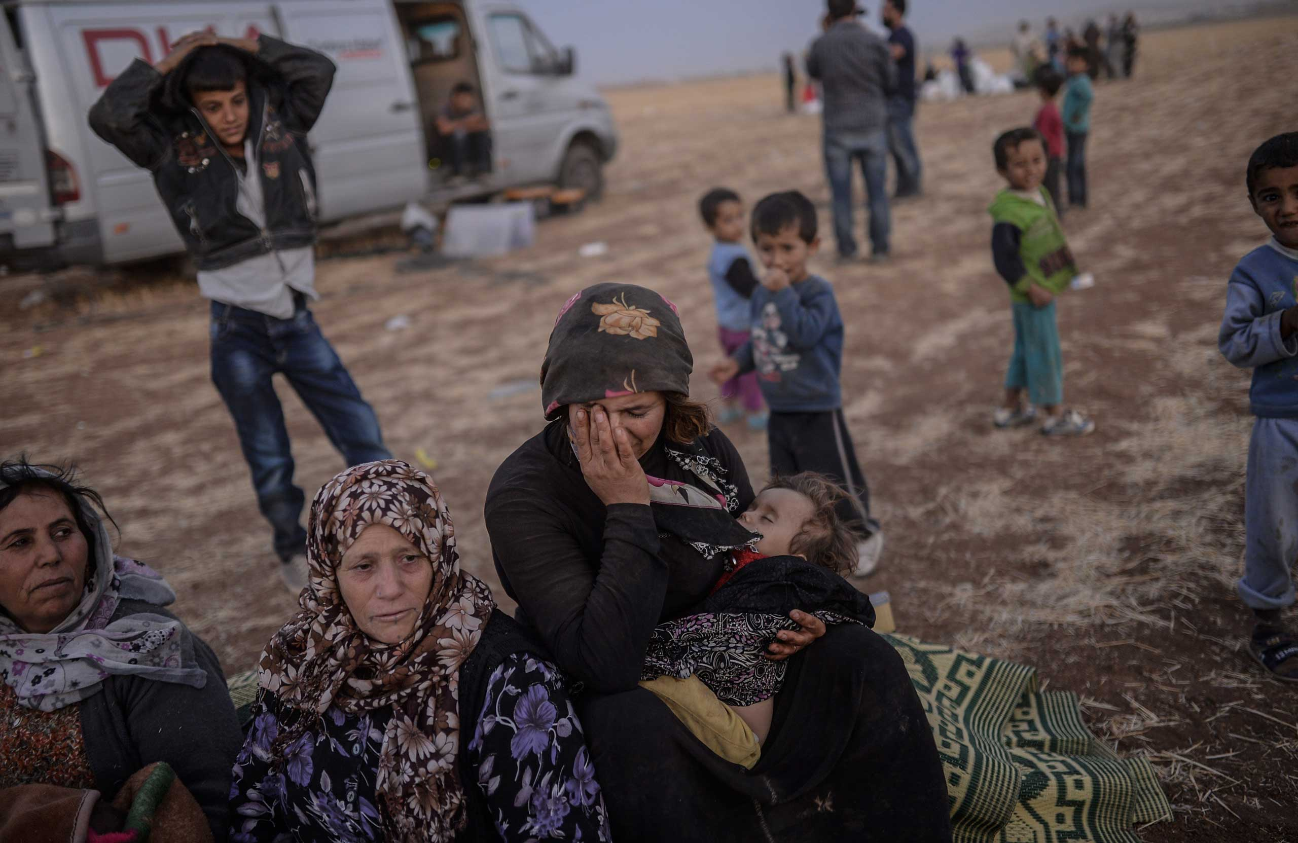 Syrian Kurds wait near the Syrian border at the southeastern town of Suruc in Sanliurfa province, on Sept. 20, 2014.