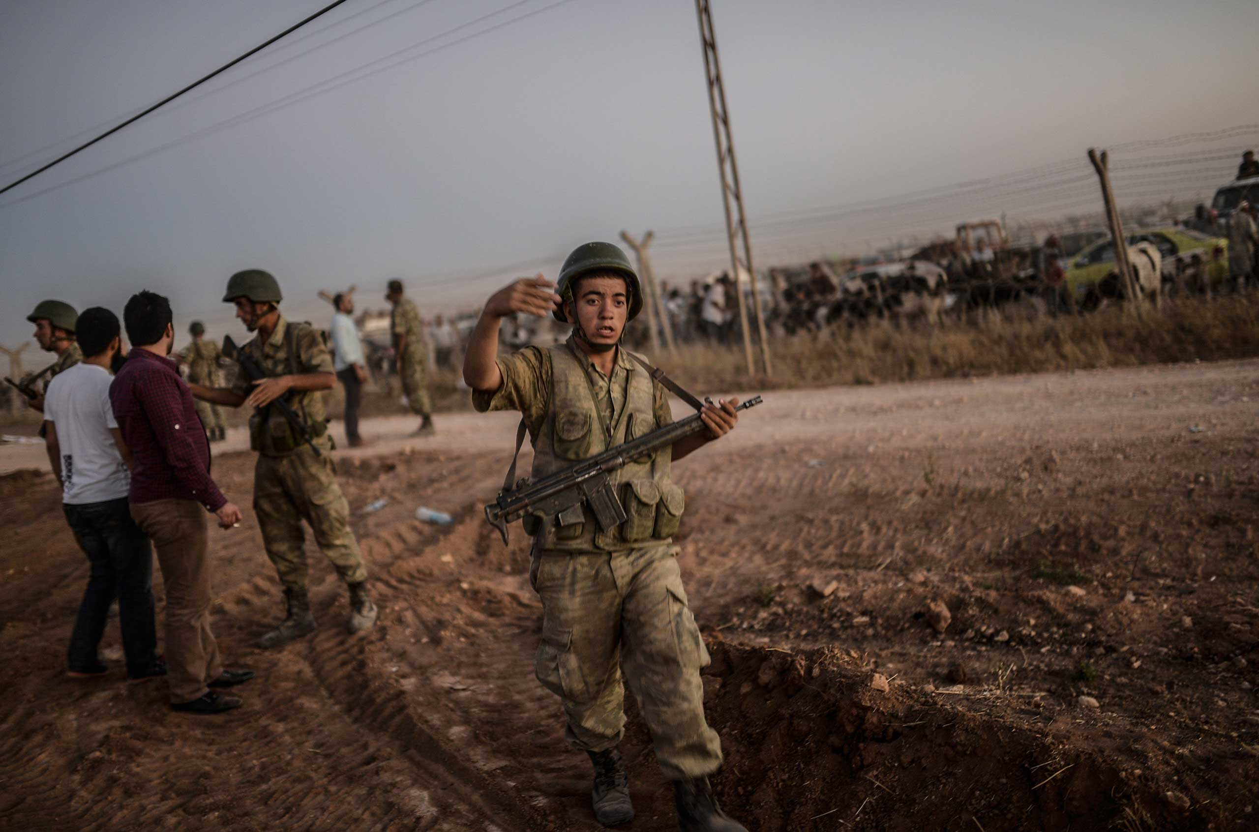 A Turkish soldier asks people to stay away from the Syrian border at the southeastern town of Suruc in Sanliurfa province, on Sept. 21, 2014.