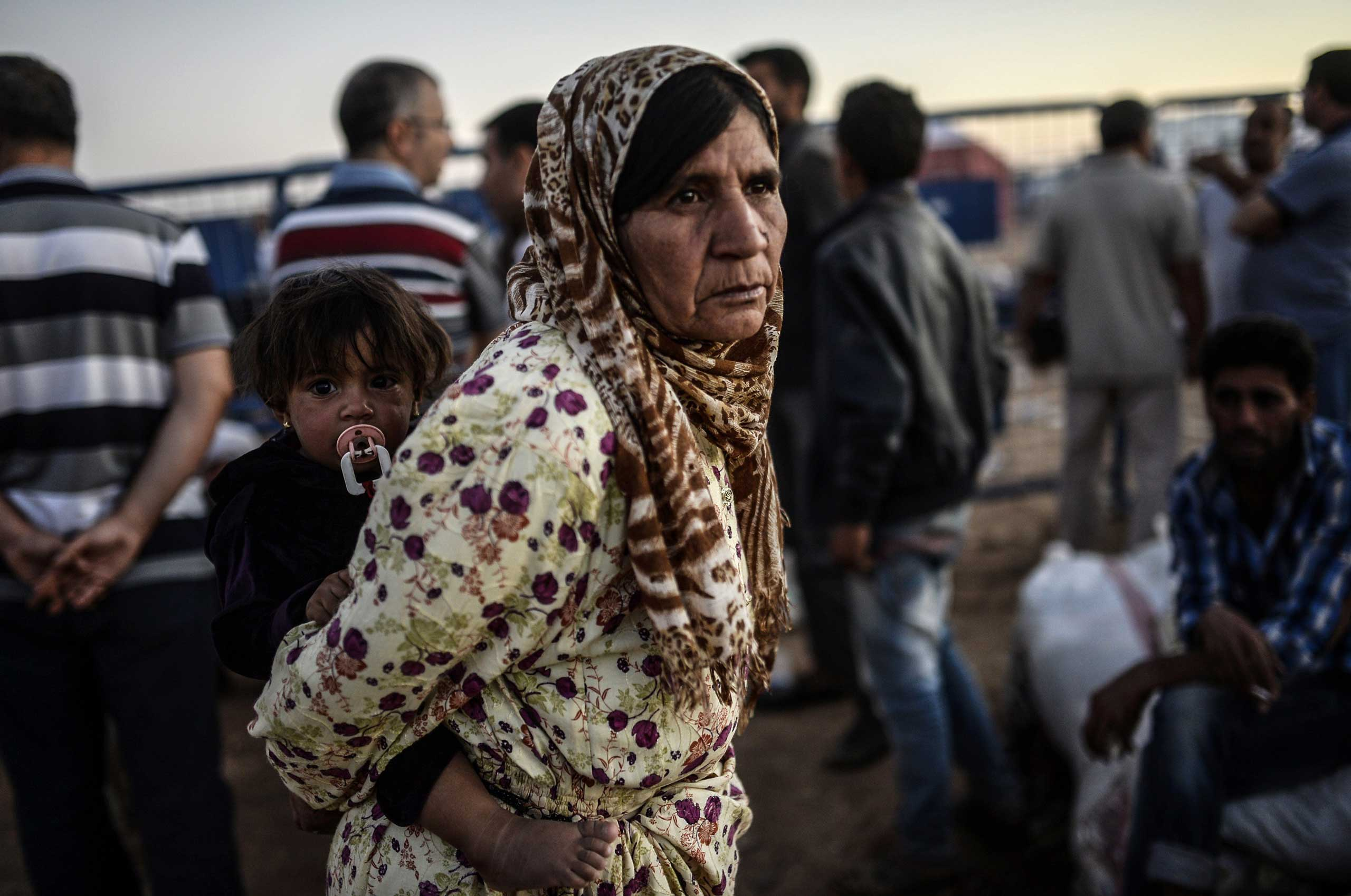 A Syrian Kurdish refugee holds a baby as she waits after crossing the border near the southeastern town of Suruc in Sanliurfa province, on Sept.  21, 2014.