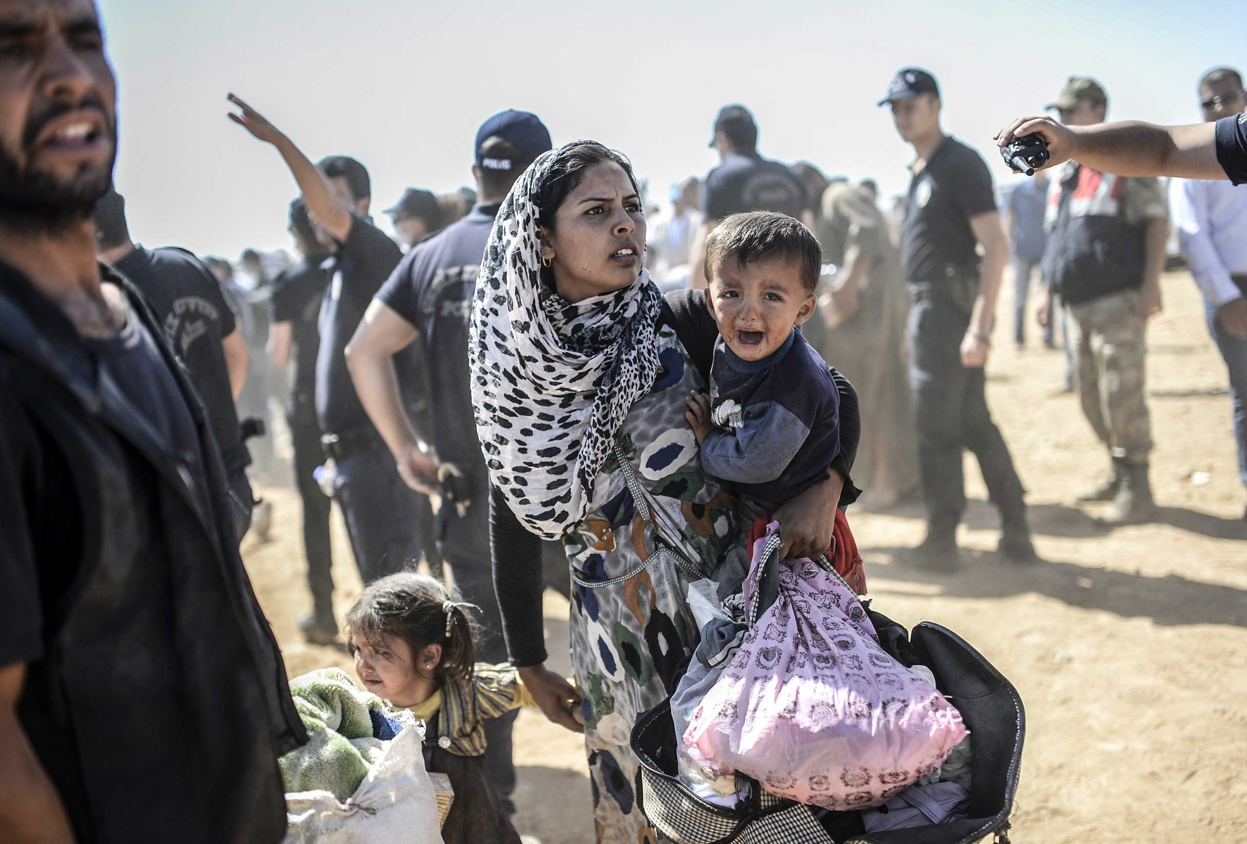 A Syrian Kurdish woman crosses the border between Syria and Turkey at the southeastern town of Suruc in Sanliurfa province on Sept. 23, 2014.