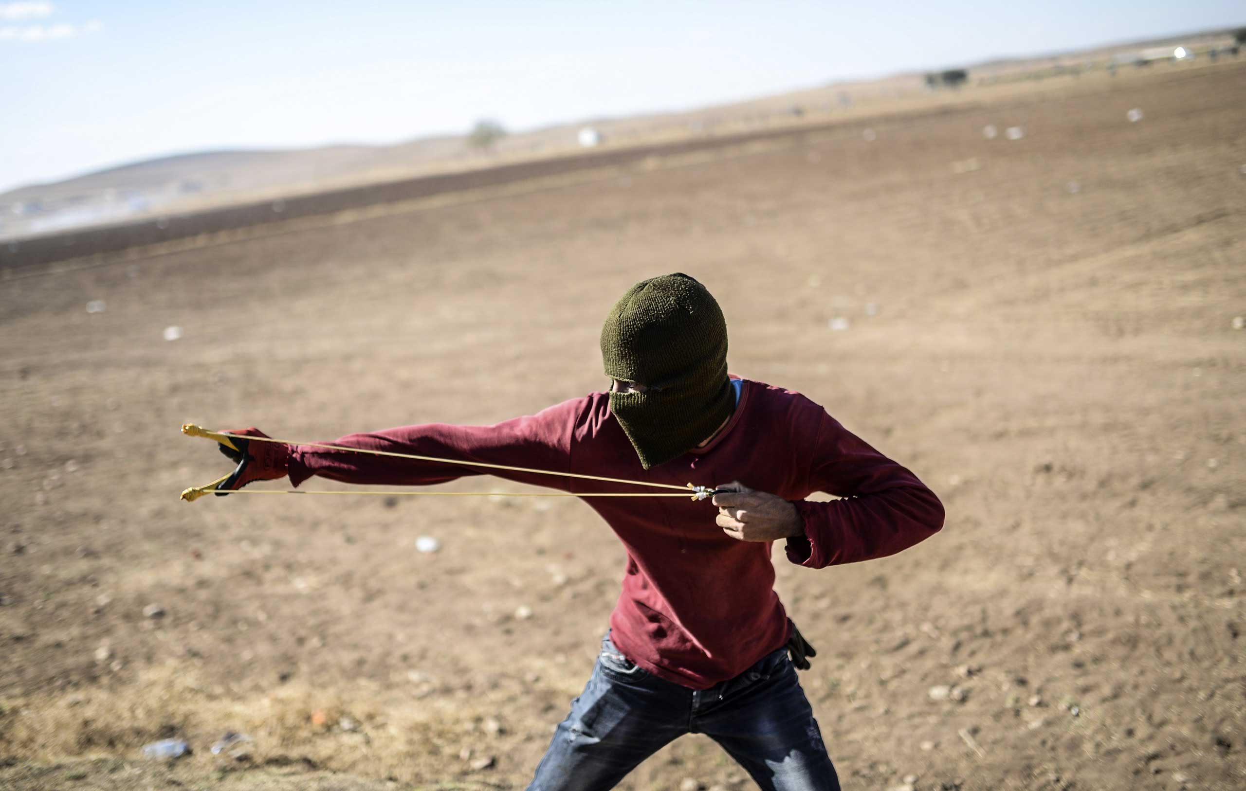 A Kurdish protestor uses a sling shot against Turkish soldiers near the Syrian border after Turkish authorities temporarily closed the border at the southeastern town of Suruc in Sanliurfa province, on Sept. 22, 2014.