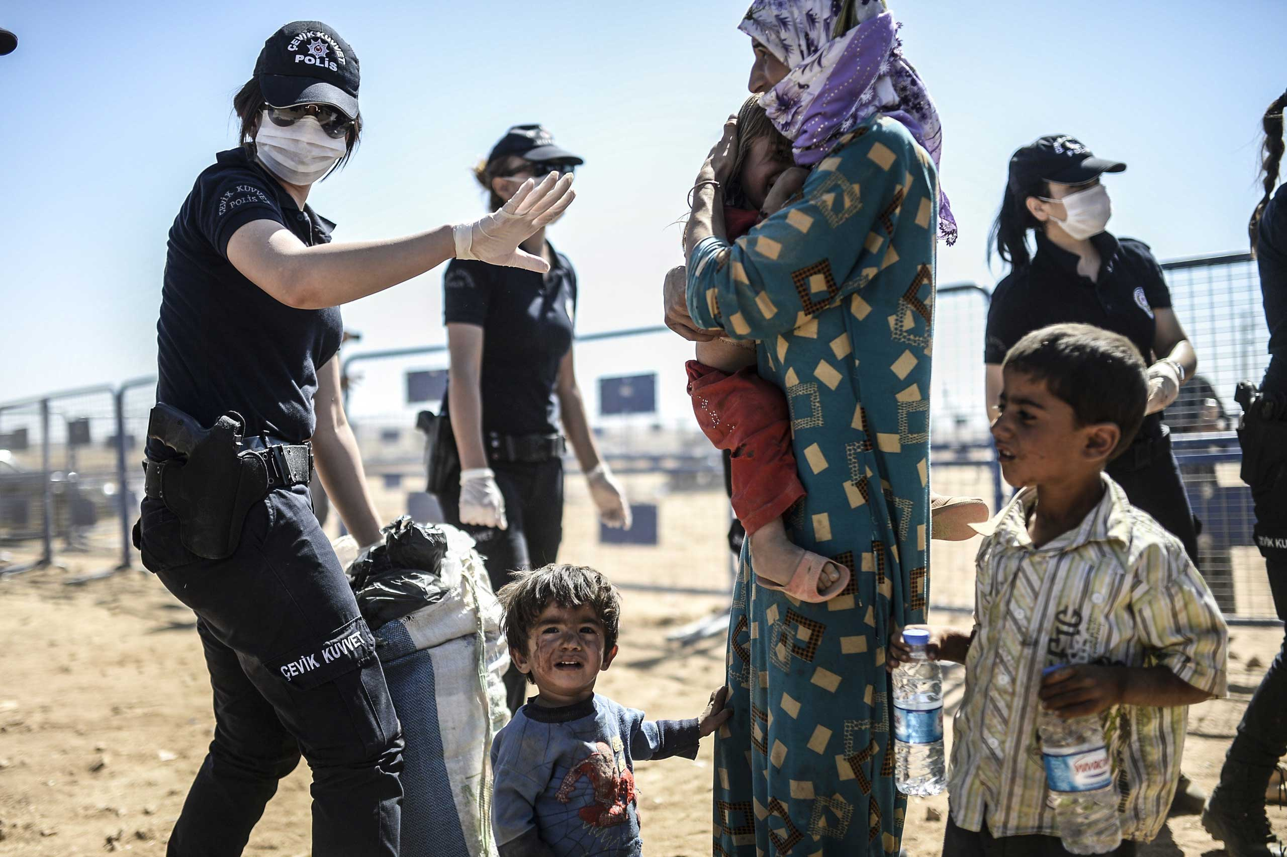 A Turkish police officer gestures as they screen Syrian Kurds crossing the border between Syria and Turkey at the southeastern town of Suruc in Sanliurfa province on Sept. 23, 2014.