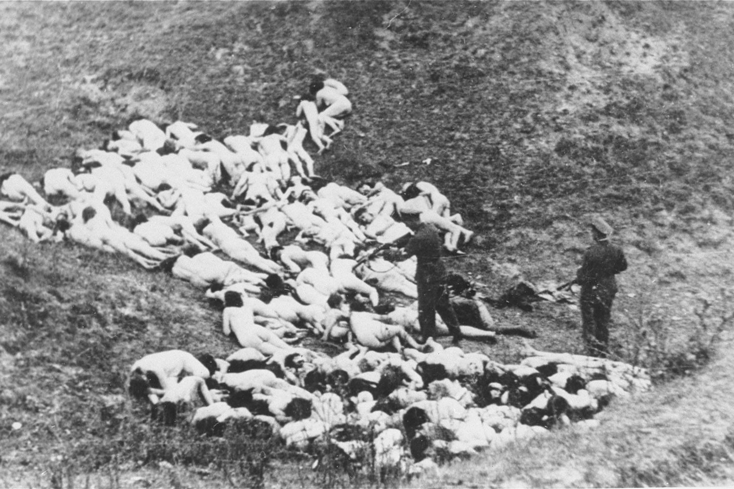 A German police officer shoots Jewish women still alive after a mass execution of Jews from the Mizocz ghetto, former Poland, 1942.
