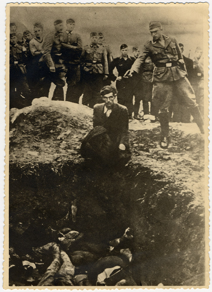 German soldiers of the Waffen-SS and the Reich Labor Service look on as a member of an Einsatzgruppe prepares to shoot a Ukrainian Jew kneeling on the edge of a mass grave filled with corpses, Vinnitsa, Ukraine, c. 1941-43.