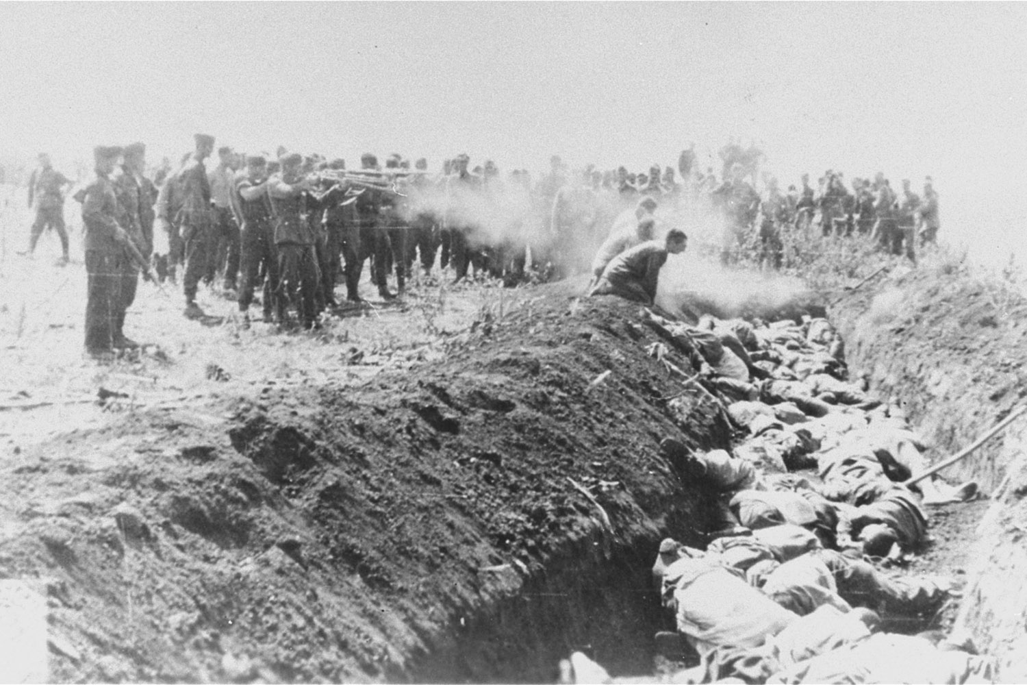 Men with an unidentified unit execute a group of Soviet civilians kneeling by the side of a mass grave, USSR, 1941.