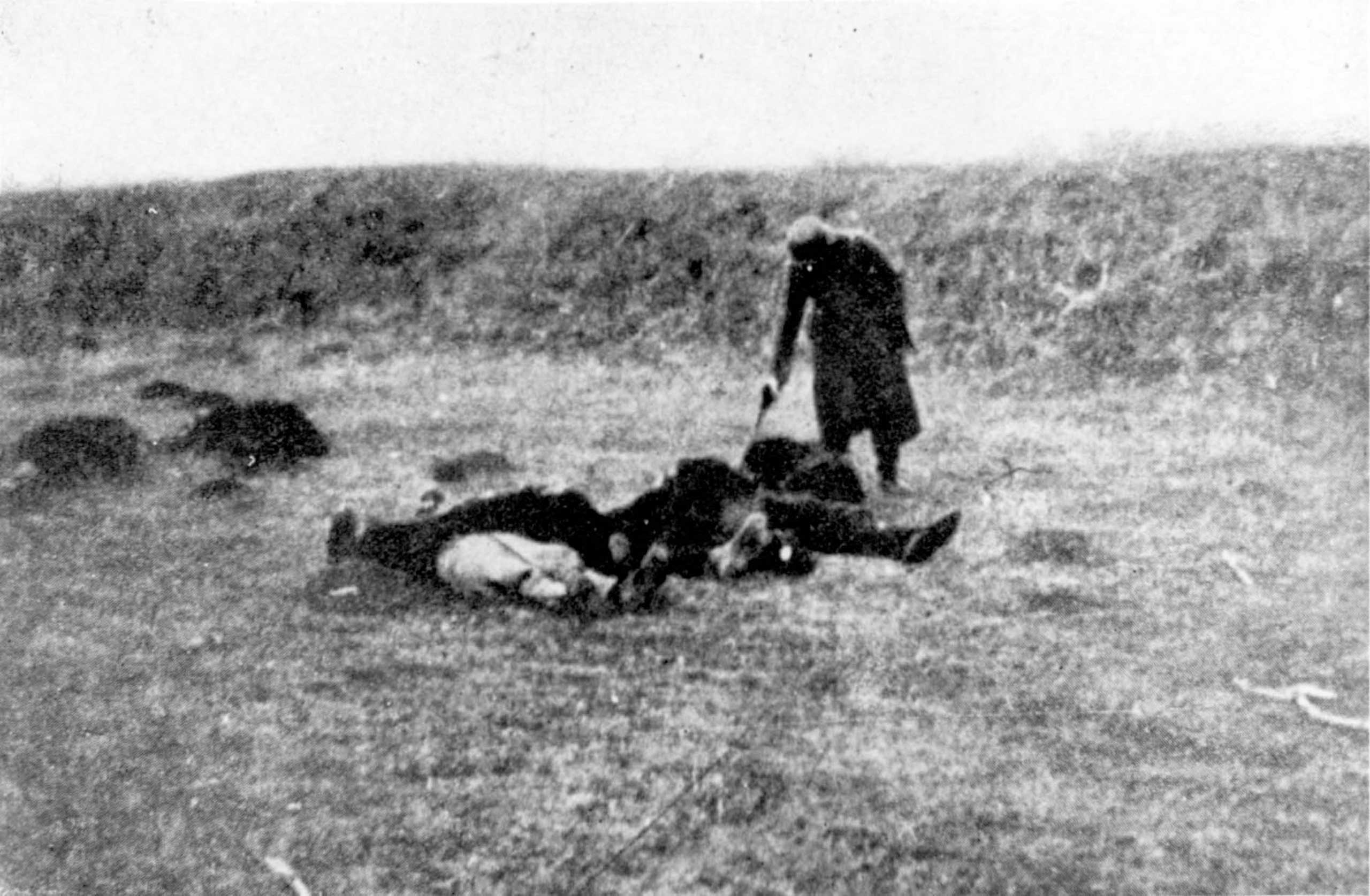 A German soldier shooting those who remained alive after a massacre in Yugoslavia, c. 1941.