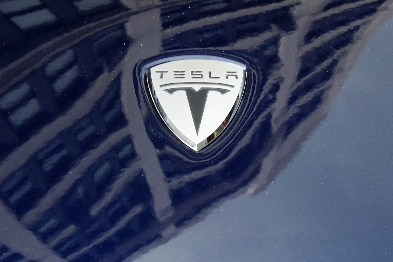 A logo of Tesla Motors on an electric car model is seen outside a showroom in New York on June 28, 2010.
