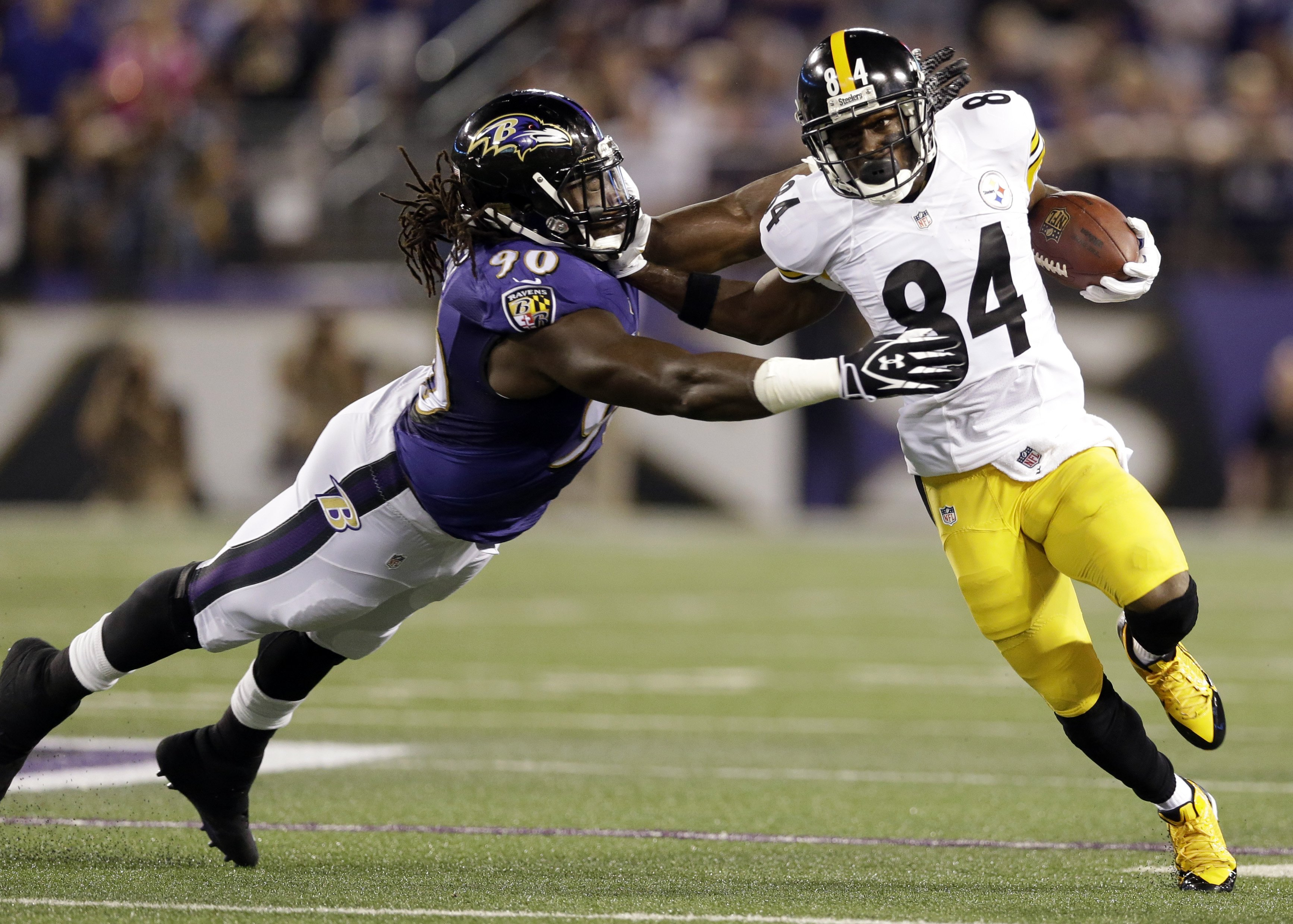 Baltimore Ravens linebacker Pernell McPhee is pushed away by Pittsburgh Steelers wide receiver Antonio Brown during the first half of an NFL football game on Sept. 11, 2014, in Baltimore.
