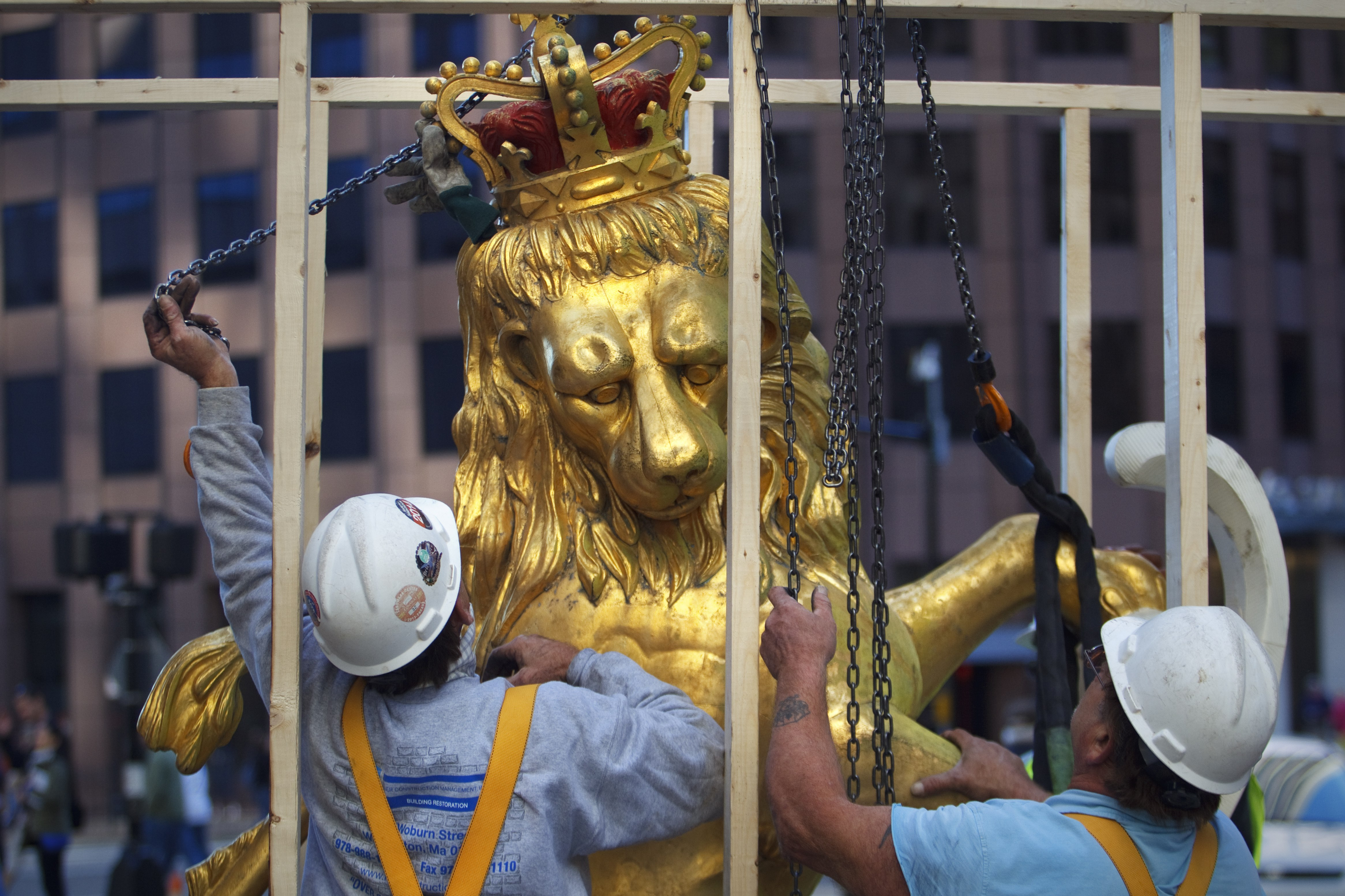 In this Sept. 14, 2014, photo, a lion statue is removed from atop the Old State House on Washington Street in Boston