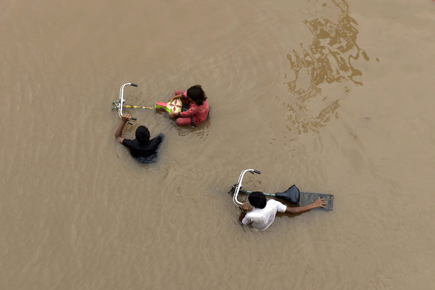 Sept. 4, 2014.                               Pakistani residents wade through floodwaters following heavy rain in Lahore, Pakistan.