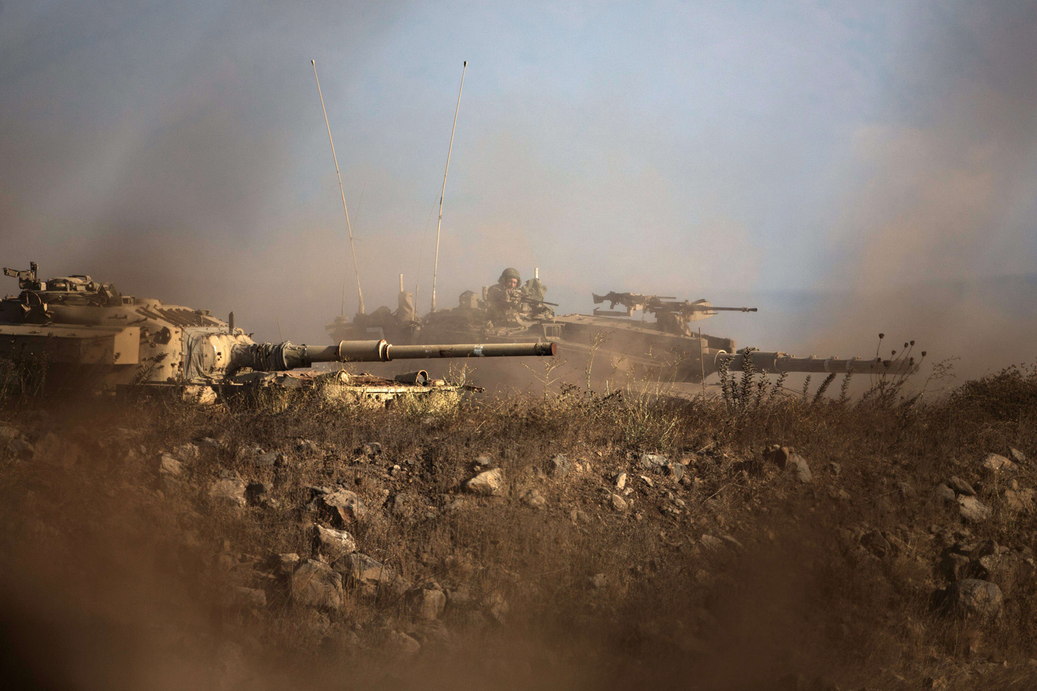 Sept. 1, 2014. An Israeli soldier sits in his Merkava tank (R) on alert position on the Israeli-annexed Golan Heights near the Quneitra crossing with Syria. Heavy fighting between Syrian government troops and opposition forces overflowed into the buffer zone separating Syrian and Israeli-occupied territory over the weekend.