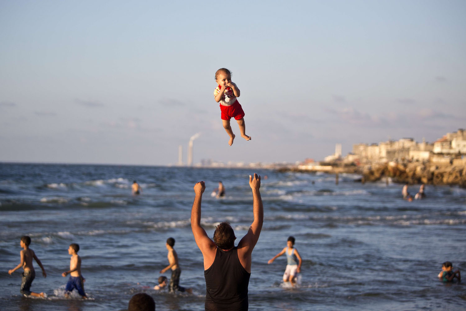 Sept. 7, 2014. A Palestinian man plays with his baby on a beach in Gaza city.