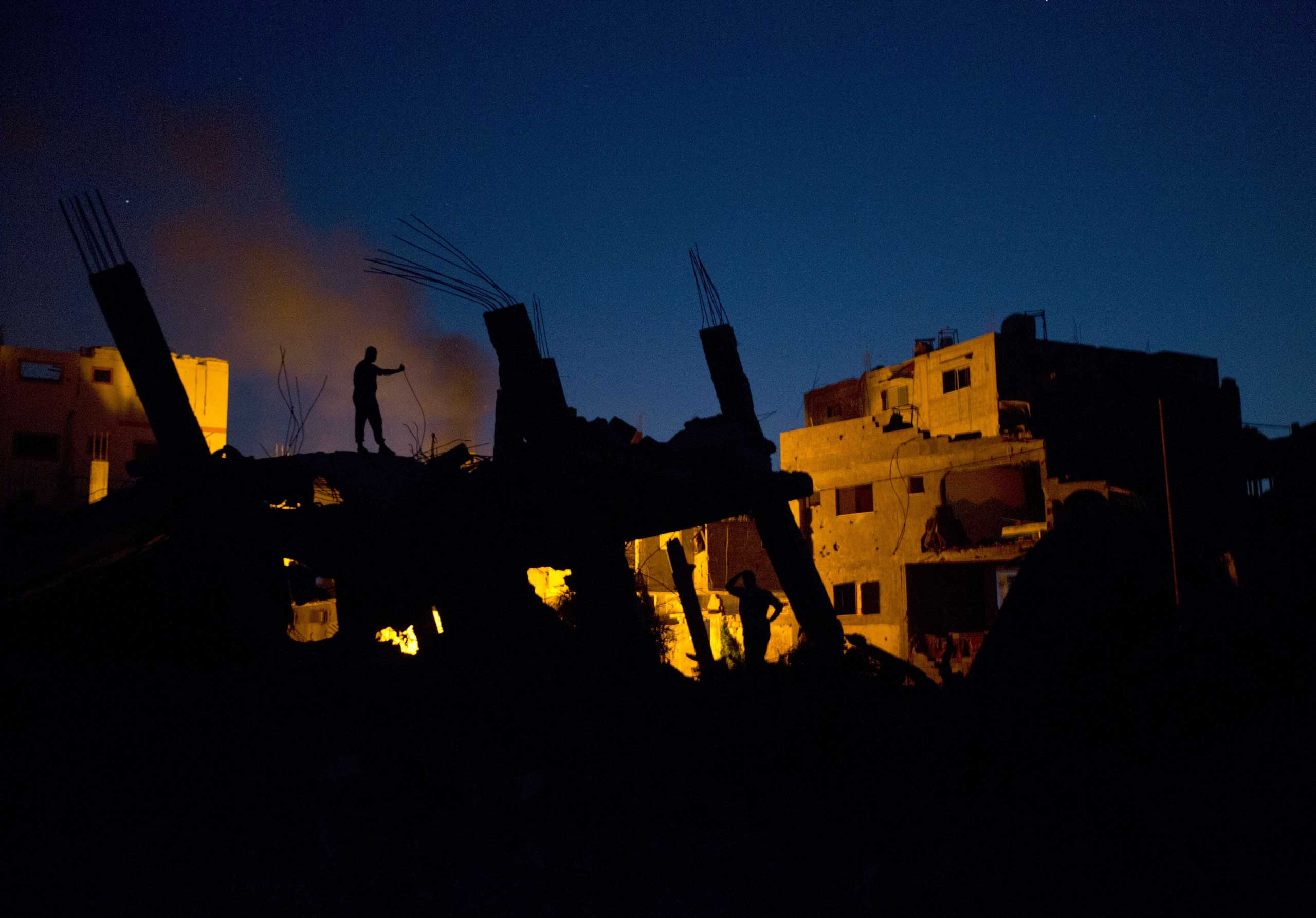 Sept.  24, 2014. Palestinian men light a fire to illuminate their neighborhood destroyed during the 50 days of conflict between Israel and Hamas, in the Shejaiya neighborhood of Gaza City.