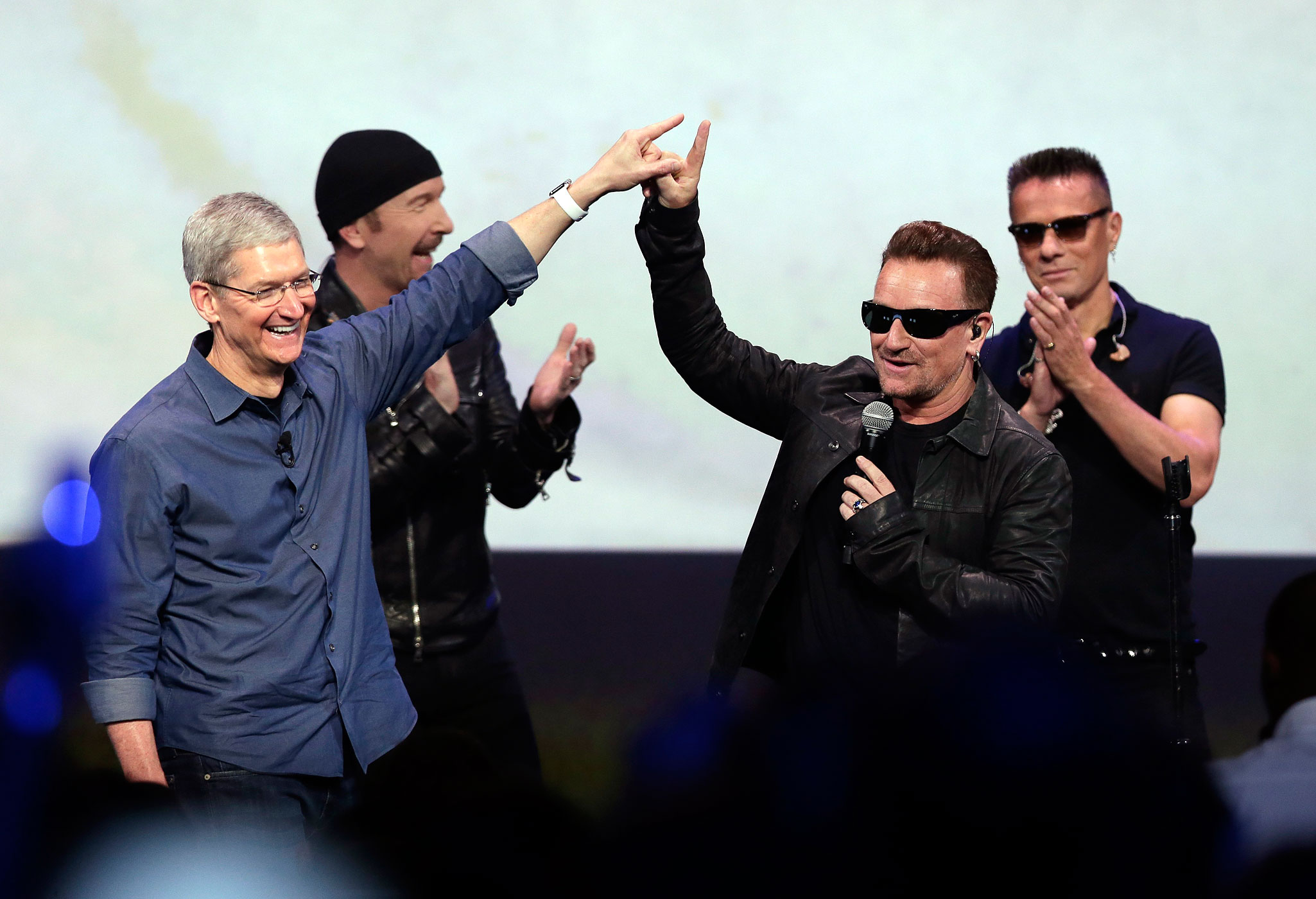 Apple CEO Tim Cook, left, greets Bono from the band U2 after they preformed at the end of the Apple event on Tuesday, Sept. 9, 2014, in Cupertino, Calif.