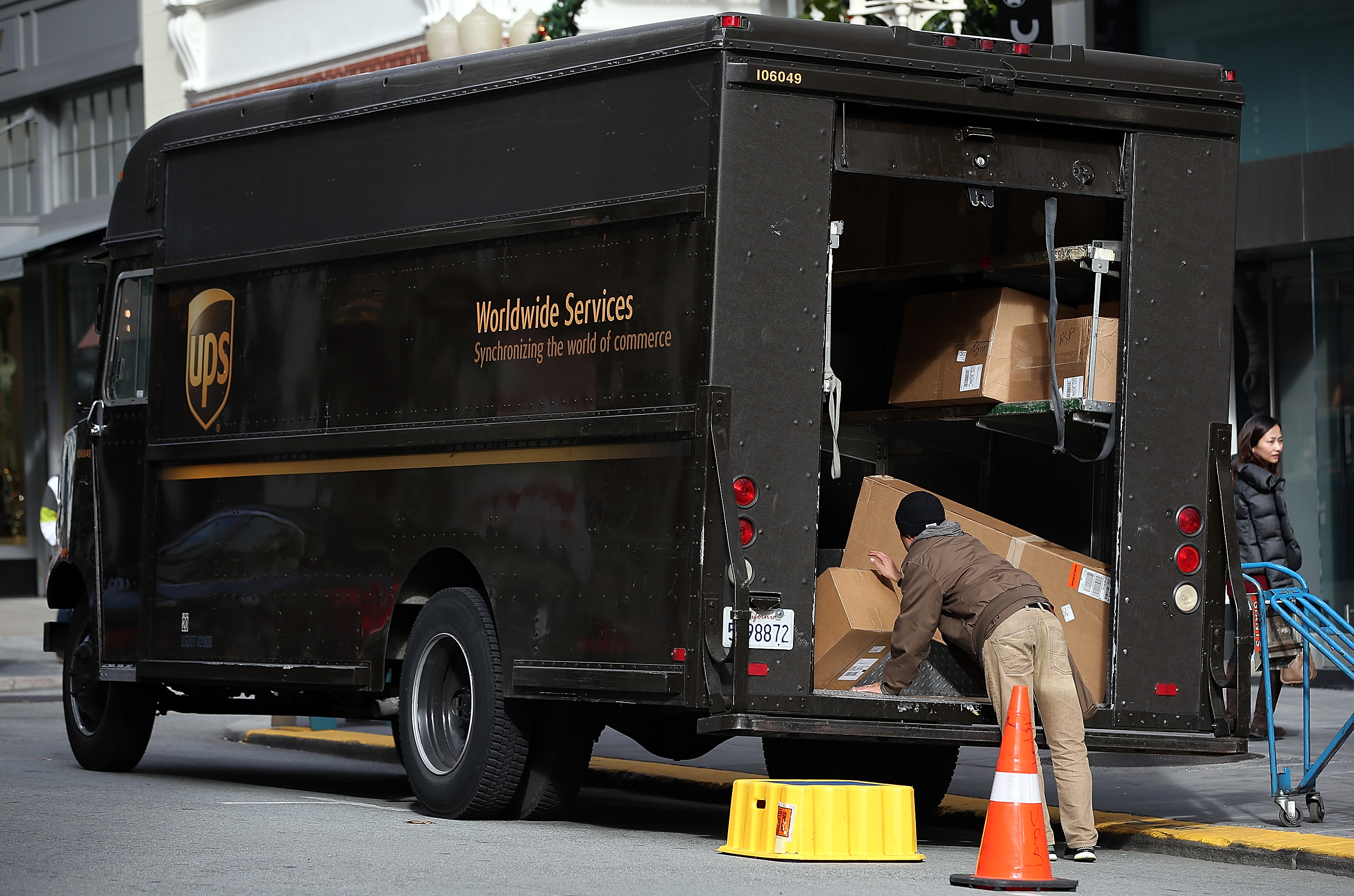 A UPS worker unloads packages from his truck on December 20, 2012 in San Francisco, California.