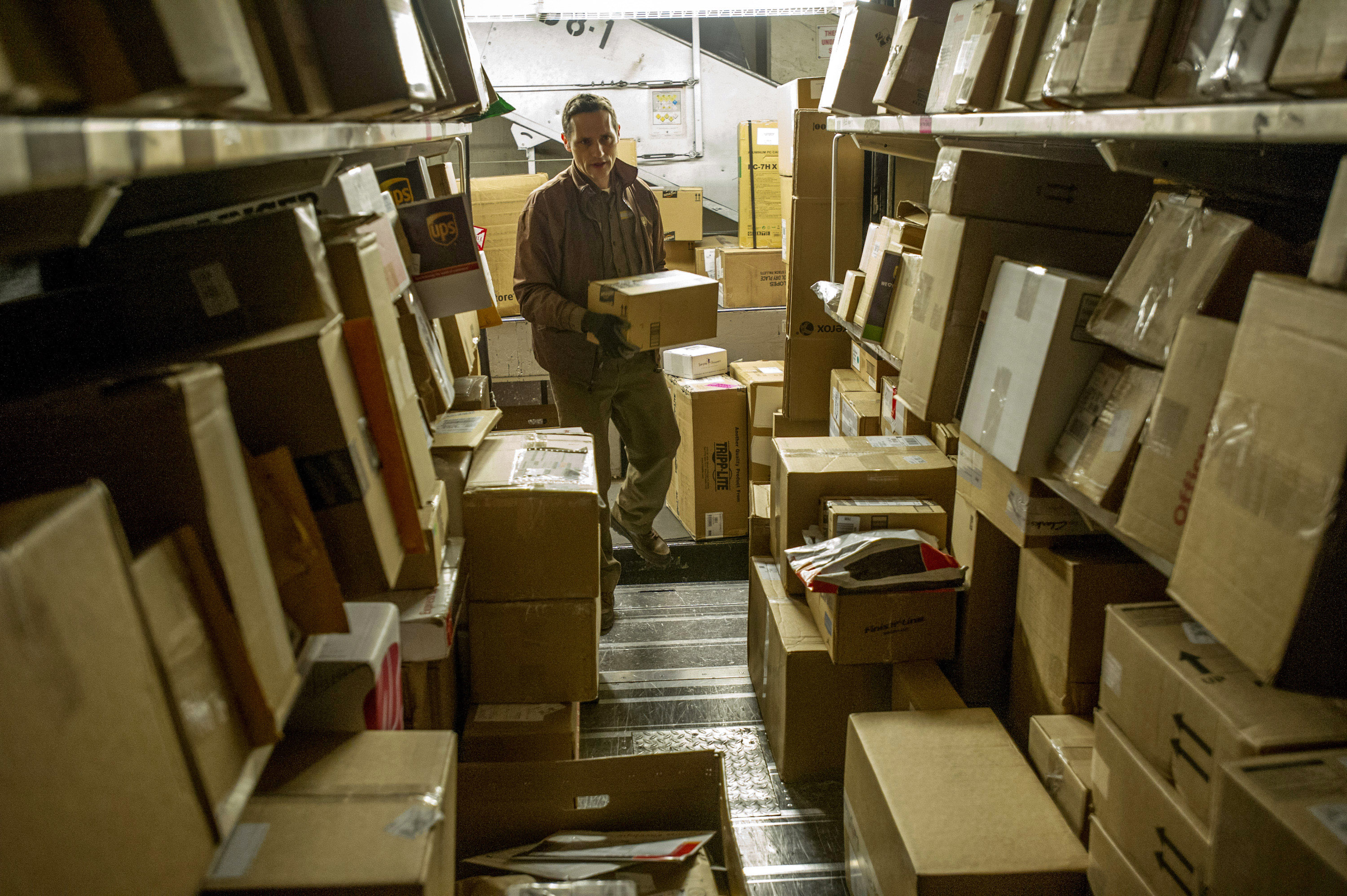 A United Parcel Service Inc. (UPS) driver loads his truck with packages at a UPS sorting facility in San Francisco, California, U.S., on Thursday, Dec. 20, 2012.
