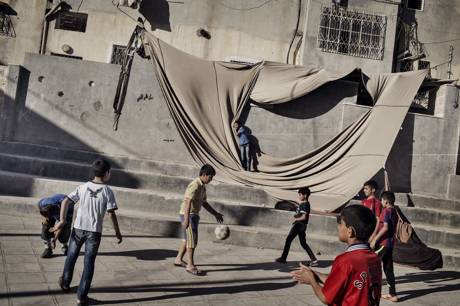 Children play soccer in a plaza in Al Fawwar, a Palestinian refugee camp in the West Bank, June 15, 2014.
