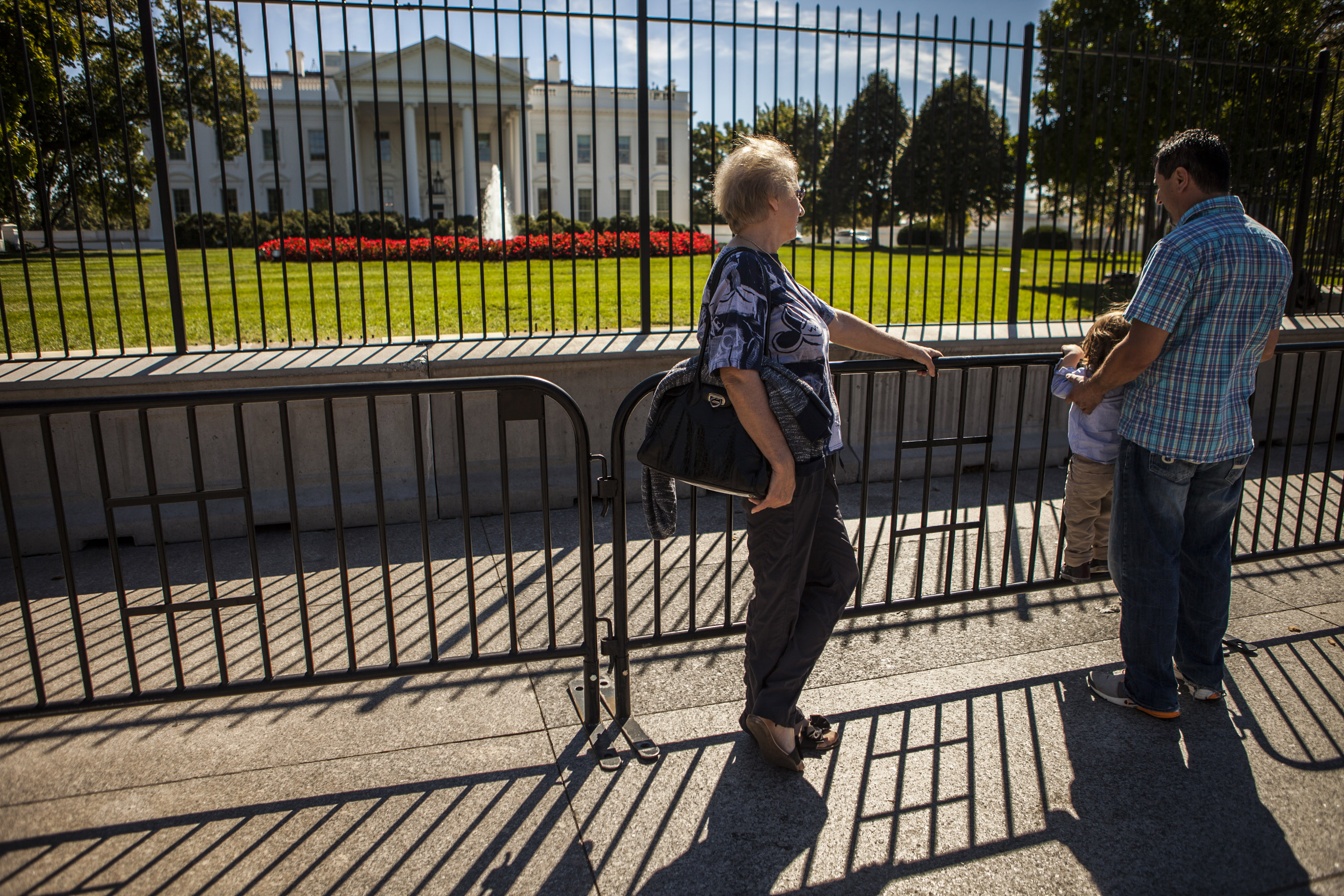 Tourists stand near the barricade that keeping visitors away from the fence outside The White House after the homeless 42-year-old man Omar Gonzales jumped the White House fence on Friday, in Washington D.C., United States on 22 September 2014.