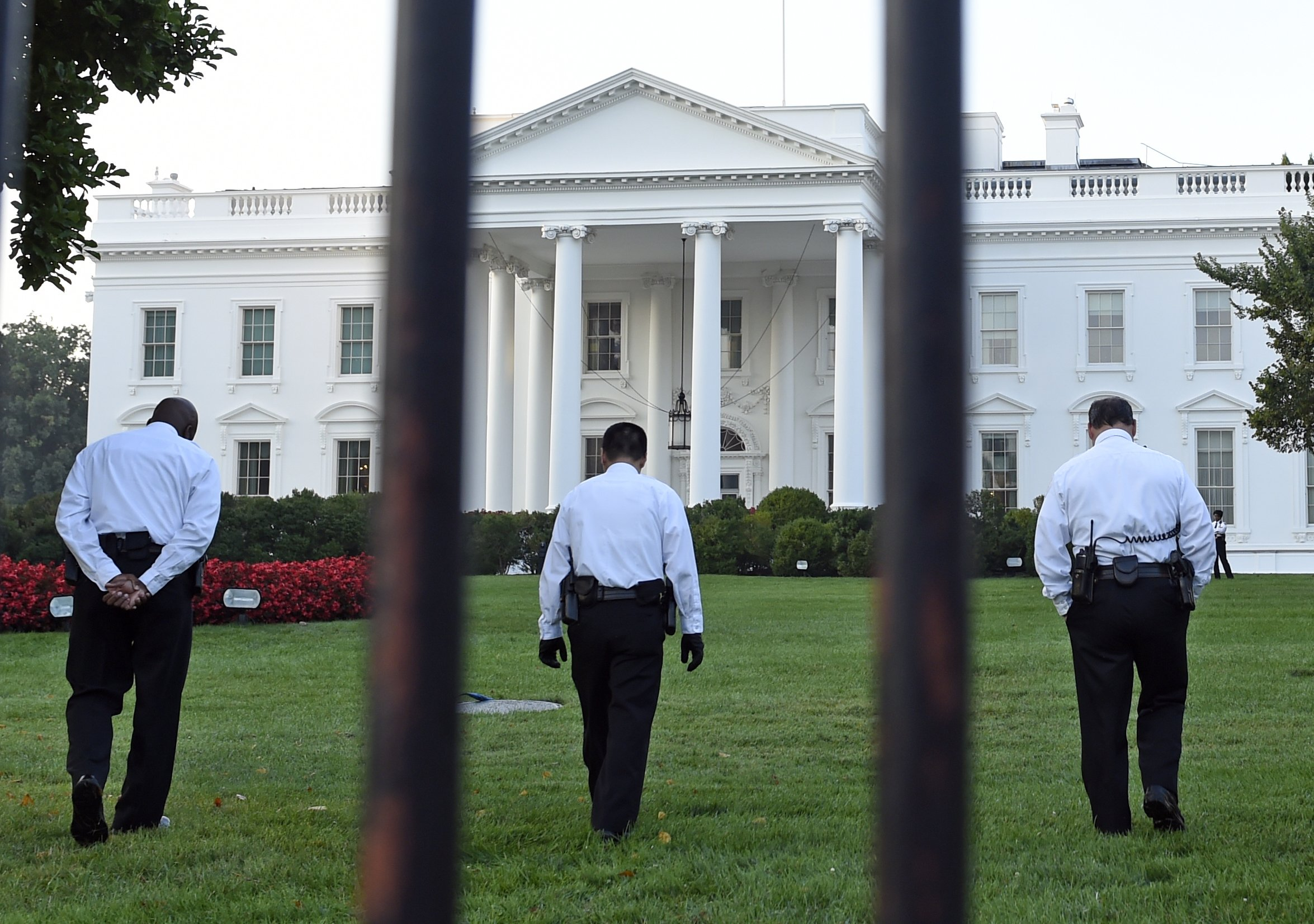 Uniformed Secret Service officers walk along the lawn on the North side of the White House in Washington on Sept. 20, 2014. The Secret Service is coming under renewed scrutiny after a man scaled the White House fence and made it all the way through the front door before he was apprehended.