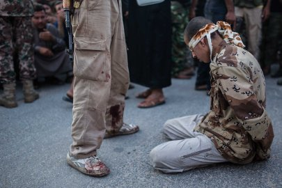 A young Syrian man kneels blindfolded before anti-regime rebels publicly executed him in the town of Keferghan, near Aleppo, on August 31, 2013.