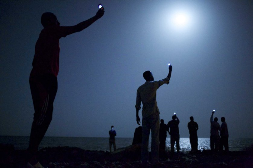 World Press Photo of the Year 2013.26 February 2013, Djibouti City, Djibouti. African migrants on the shore of Djibouti city at night, raising their phones in an attempt to capture an inexpensive signal from neighboring SomaliaÑa tenuous link to relatives abroad. Djibouti is a common stop-off point for migrants in transit from such countries as Somalia, Ethiopia and Eritrea, seeking a better life in Europe and the Middle East.