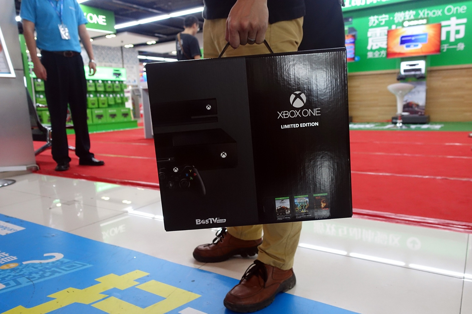 A customer holds Microsoft's Xbox One game console limited edition in an electronic shop in Shanghai on September 29, 2014.