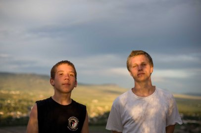 Brothers Vinny and David stand together as the sky darkens before a summer storm.