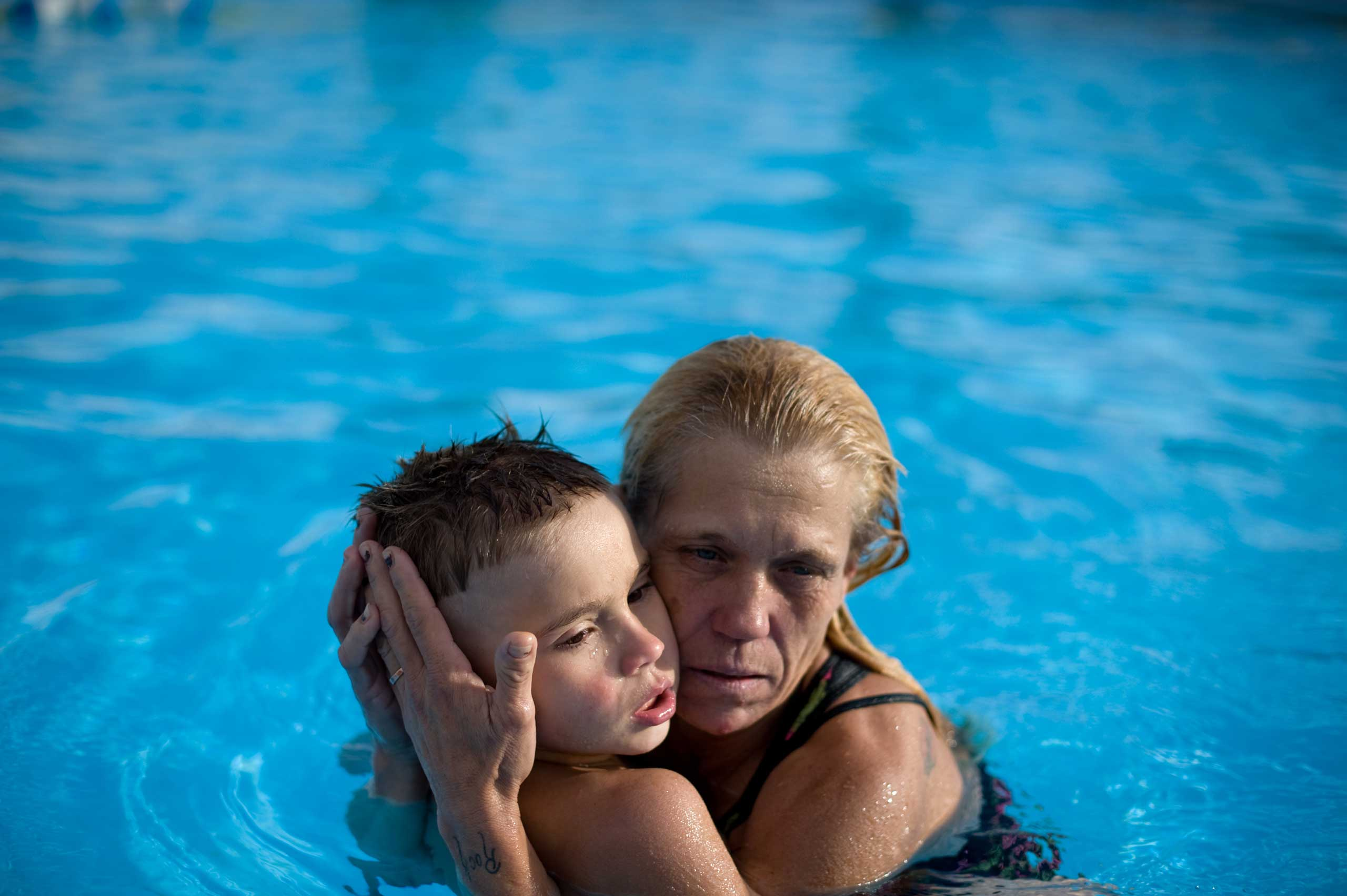 Eve holds Michael in the pool at a motel.