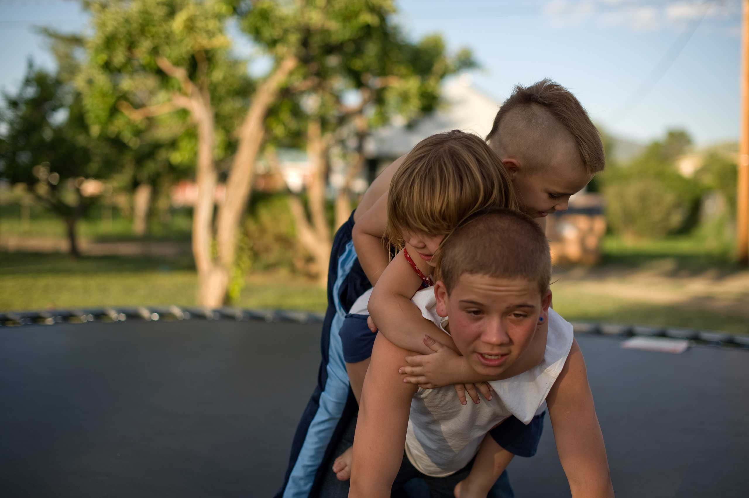 Vinny, Michael and Elycia play together on a trampoline. This is Vinny's first visit with his siblings since beginning his new life with his aunt.