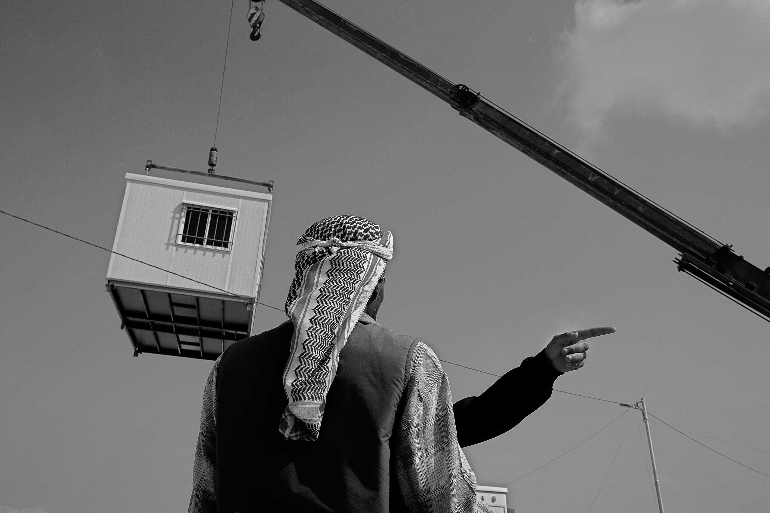 December 2013. Za'atari refugee camp, Jordan. A Syrian refugee watches a prefabricated unit being delivered to replace makeshift tents.