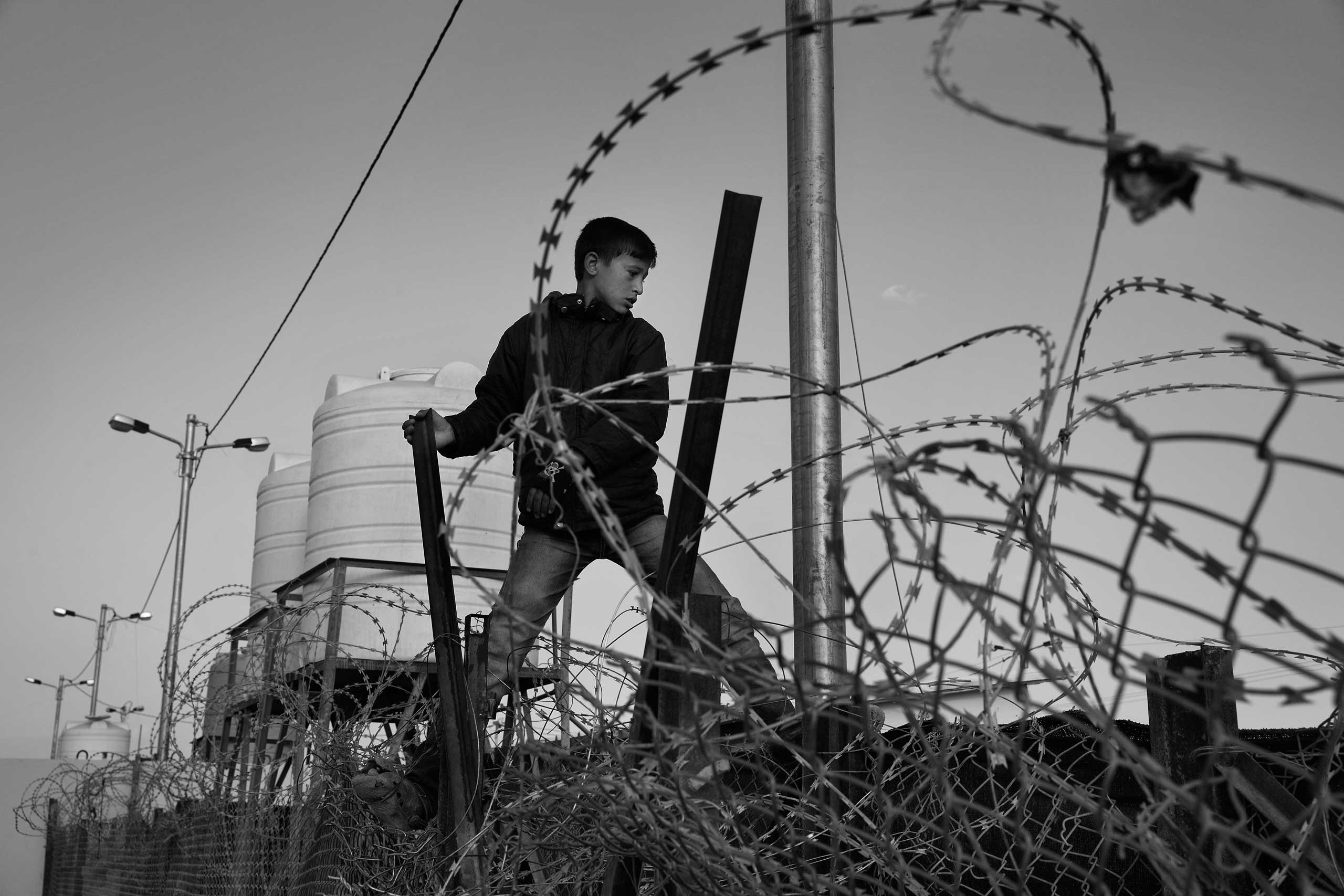 December 2013. Za'atari refugee camp, Jordan. Boys climb the fences to reach the newly arrived refugees and sell them bread, cigarettes and tea.