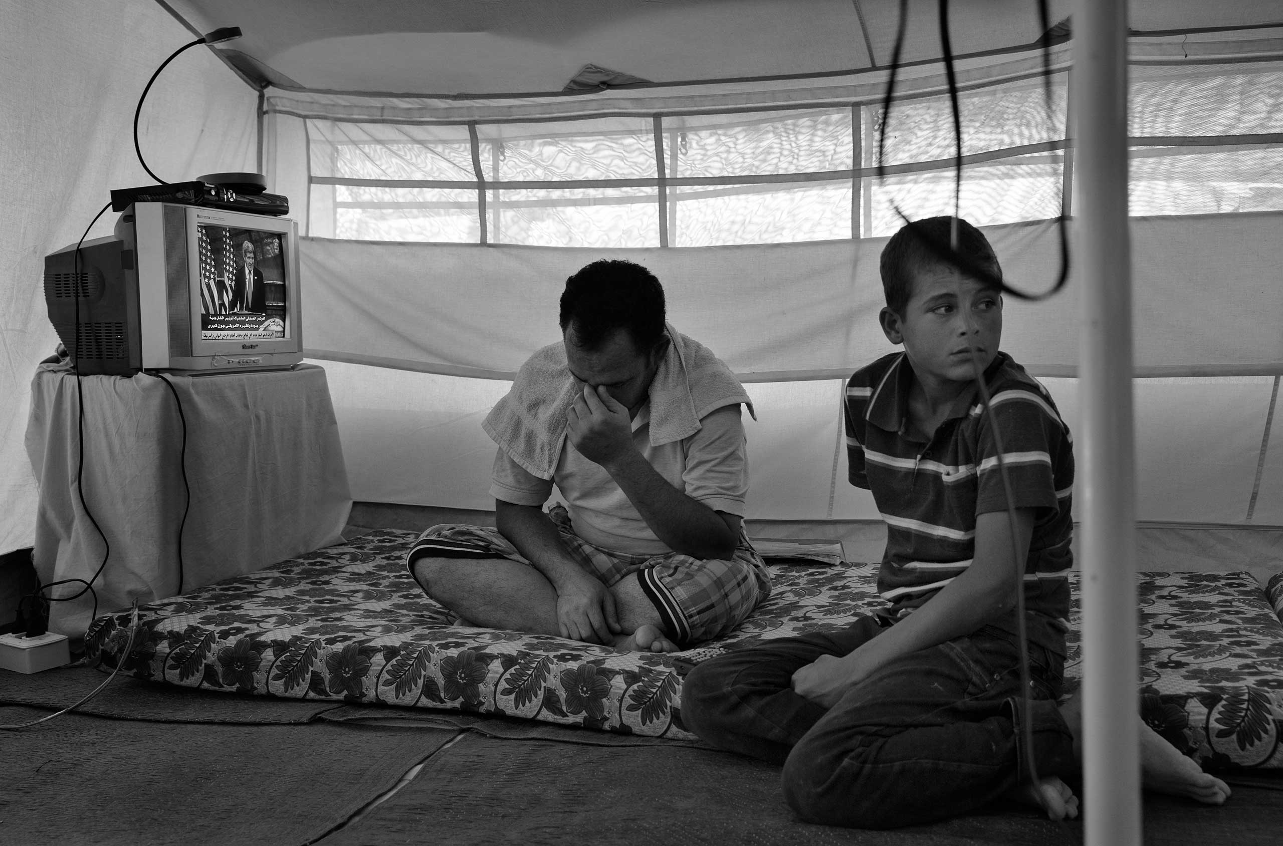 December 2013. Za'atari refugee camp, Jordan. A father and son in a camp tent.