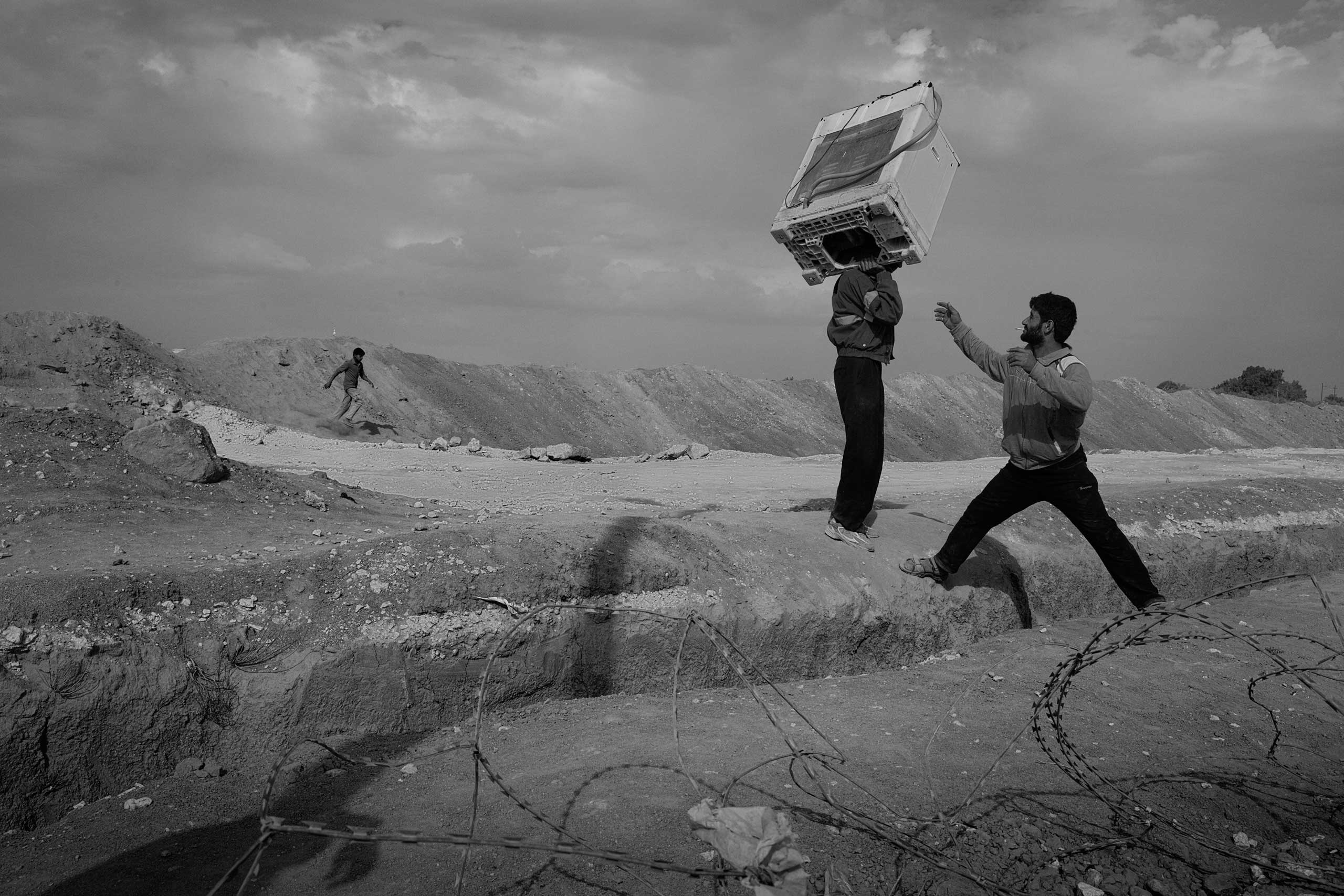 December 2013. Za'atari refugee camp, Jordan. Refugees carry an oven into the camp after bartering or selling goods for it in Jordan.