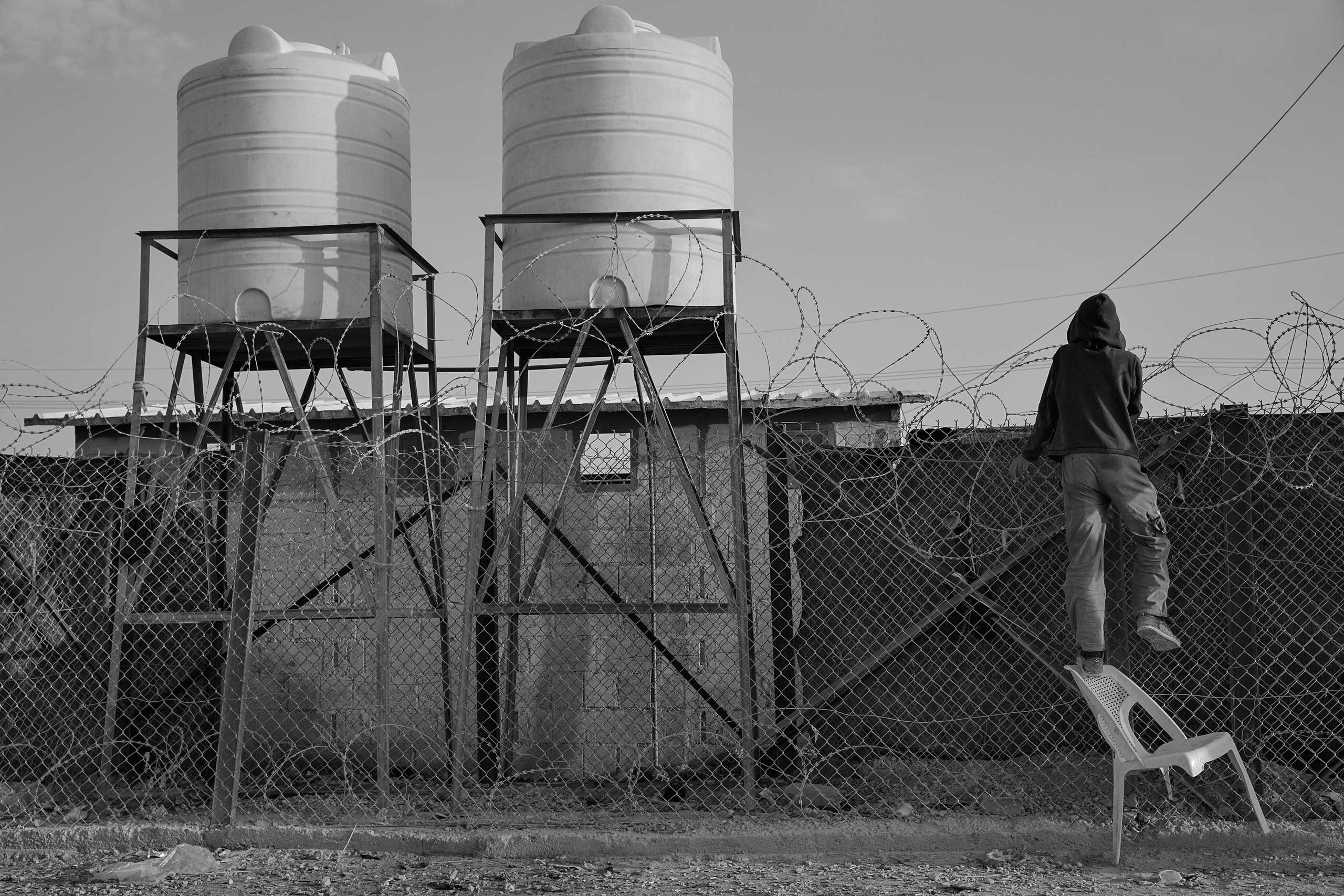 December 2013. Za'atari refugee camp, Jordan. Boys living in the camp climb the fence of the United Nations High Commissioner for Refugees' compound where newly arrived refugees are gathered in the early hours of the morning.