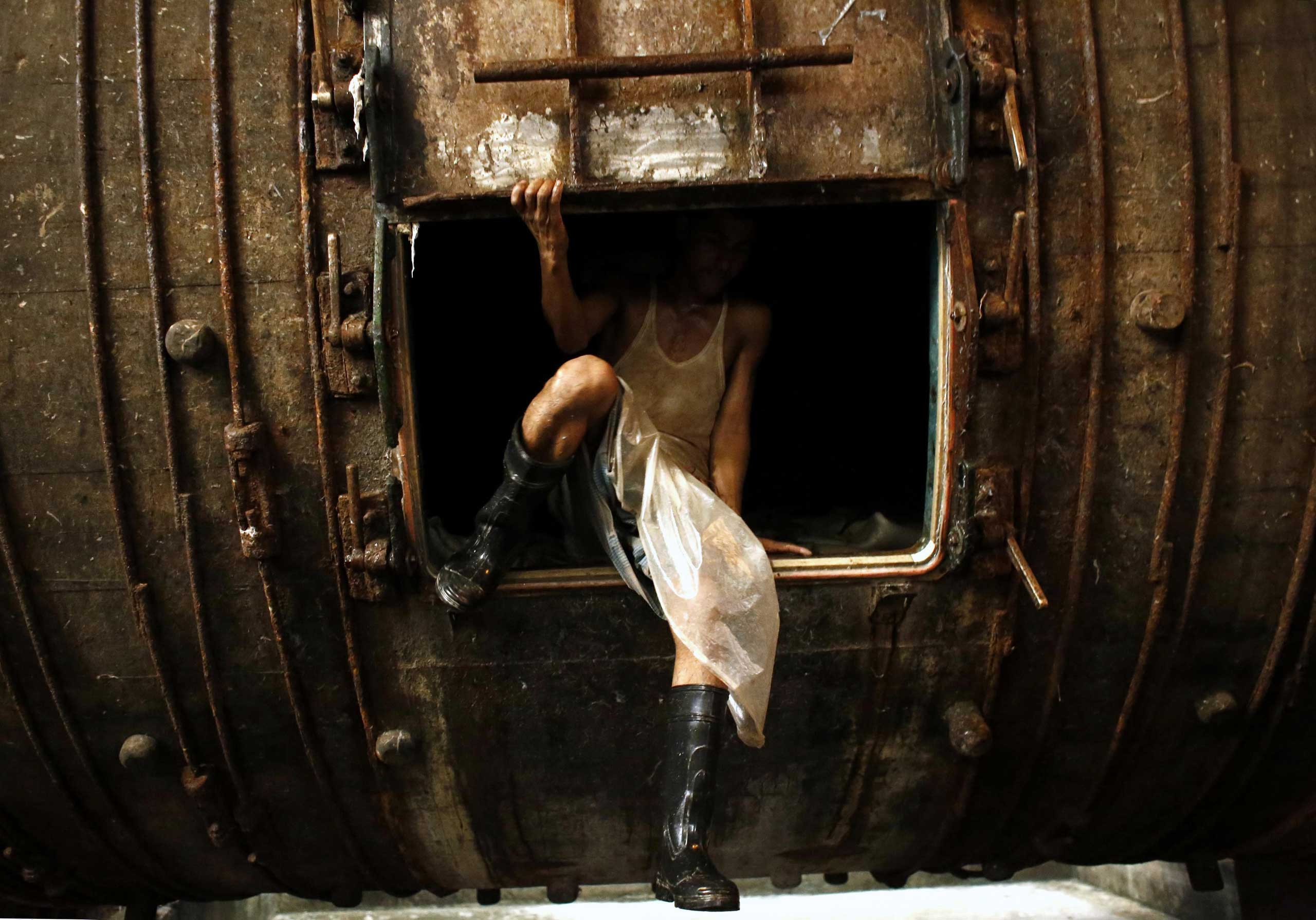 Oct. 8, 2014. A Worker comes out of a tank as he processes animal skins slaughtered during the Eid Al Adha, at a Leather factory in Hazaribagh, Dhaka, Bangladesh.