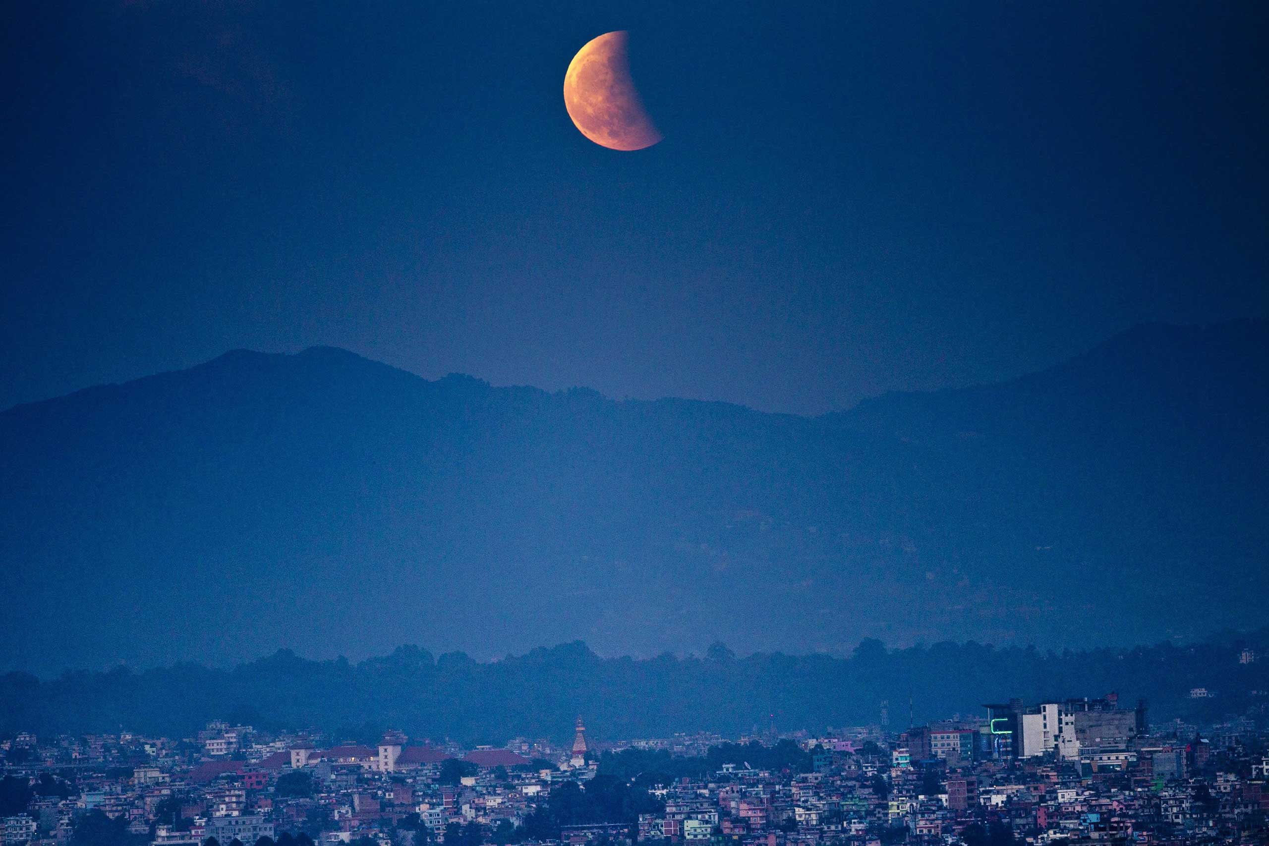 The moon is seen glowing red as it rises in Kathmandu, Nepal during a total lunar eclipse.