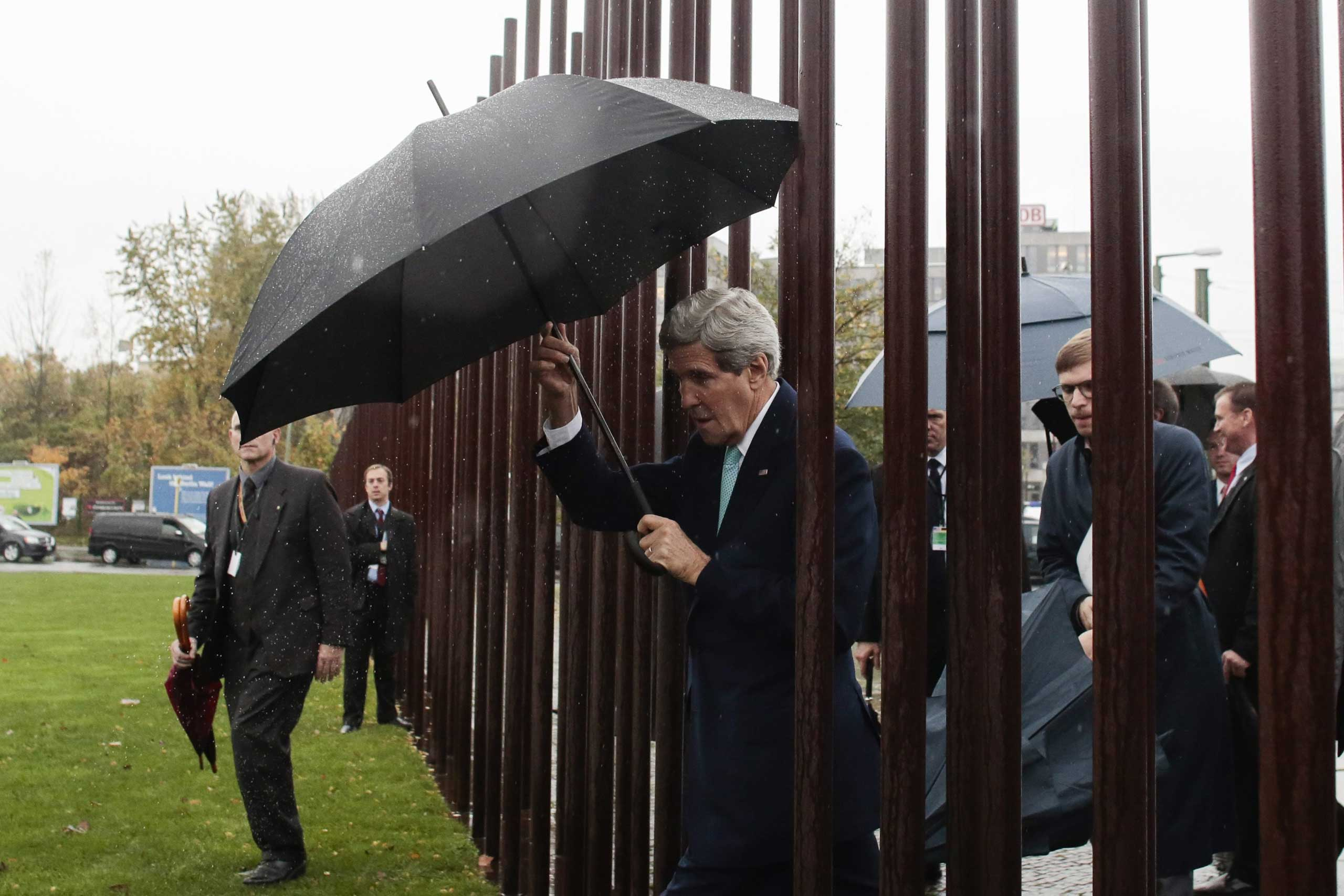 OCt. 22, 2014. United States Secretary of State John Kerry (C) walks with an umbrella as he visits the Berlin Wall memorial site prior to a news conference with German Foreign Minister Frank-Walter Steinmeier at the Wall Documentation Center in Berlin, Germany.