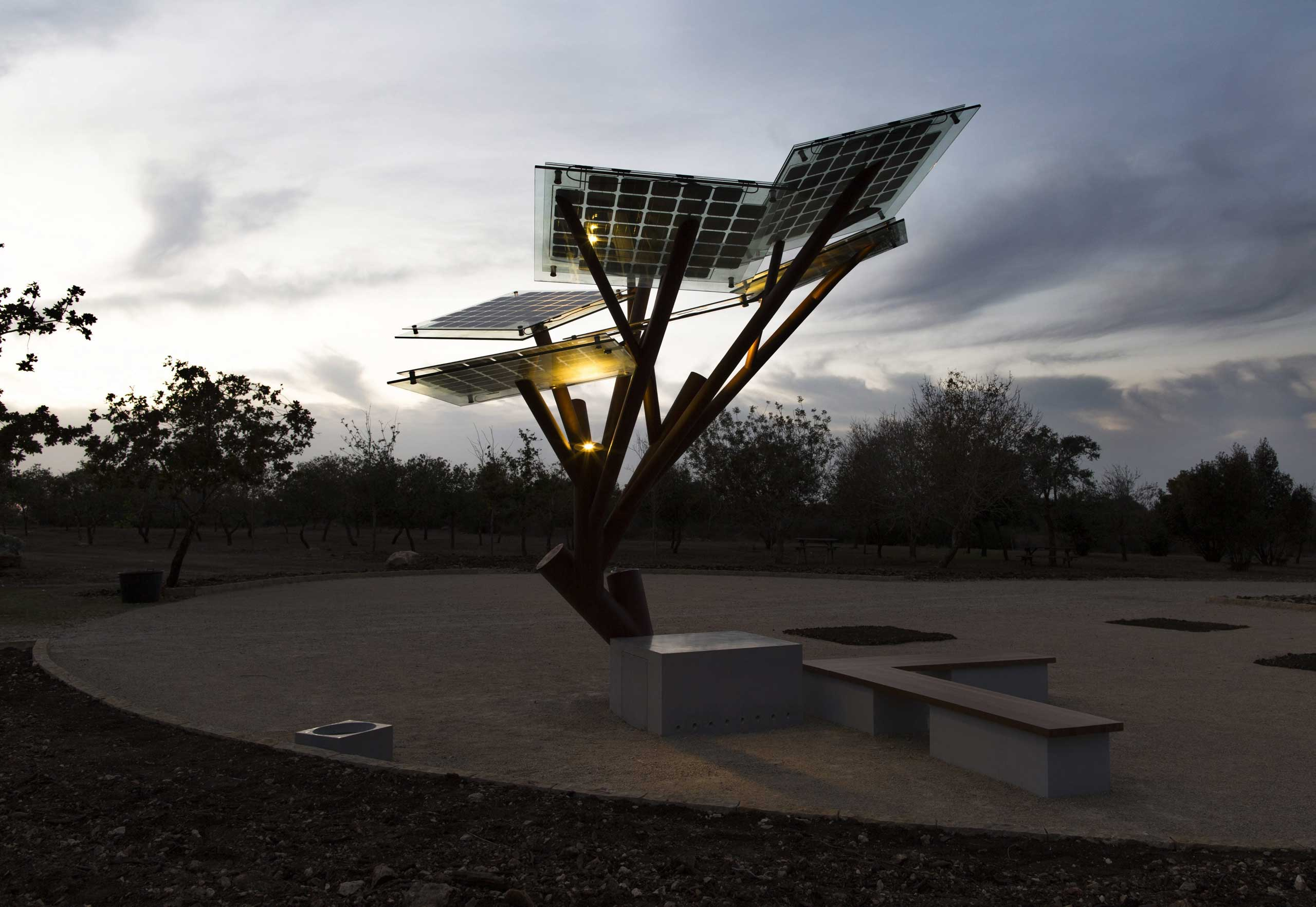 Oct. 22, 2014. The lights of the eTree come on as it gets dark at the prototype unit set up in a park in Zichron Yacov, northern Israel. The eTree is billed as an ecological sculpture assembling a real tree whose canopy is made up of solar panels producing energy from the sun. In addition to offering shade it provides a drinking fountain, free WiFi, a docking station to charge smartphones and tablets, and outlets for electrical appliances. It also has a water dish for dogs and lights that come on when it becomes dark. The next unit will be placed in Nice, France.